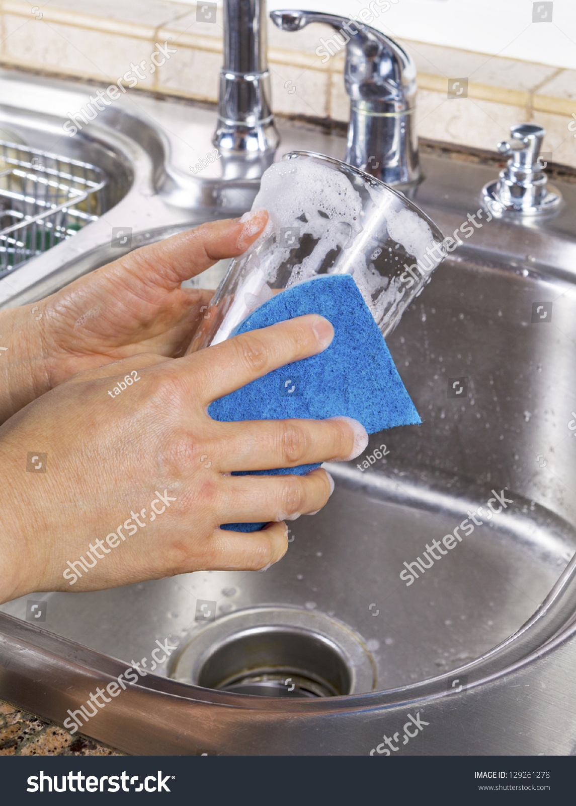 vertical photo of female hands cleaning a drinking glass with soapy water and a sponge with. Black Bedroom Furniture Sets. Home Design Ideas