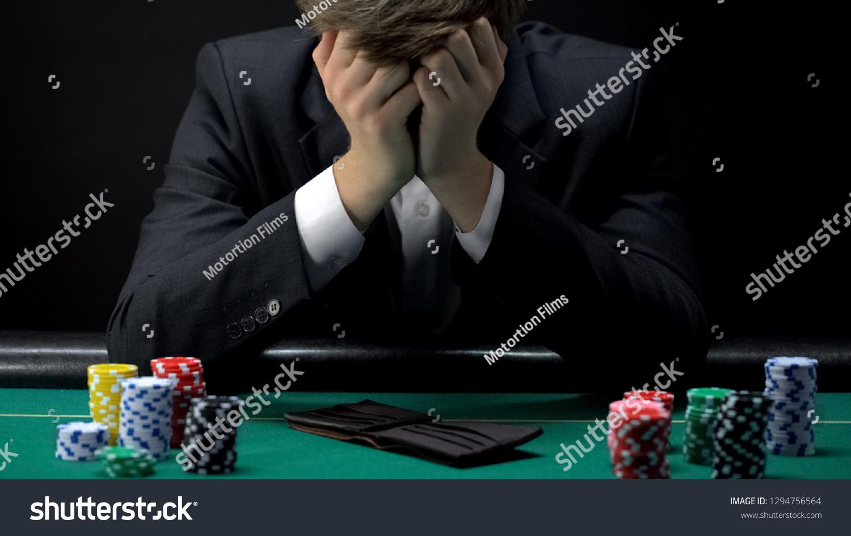 Young devastated businessman losing poker game at casino, gambling addiction #1294756564