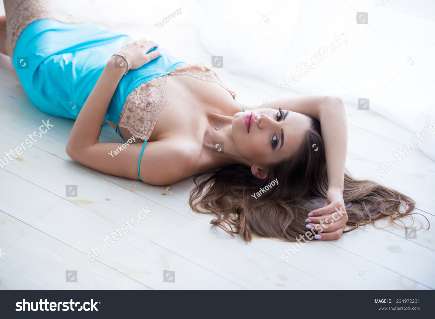 f9efb50848 Beautiful young woman in blue nightgown peignoir girl lying on the bed on a  white sheet