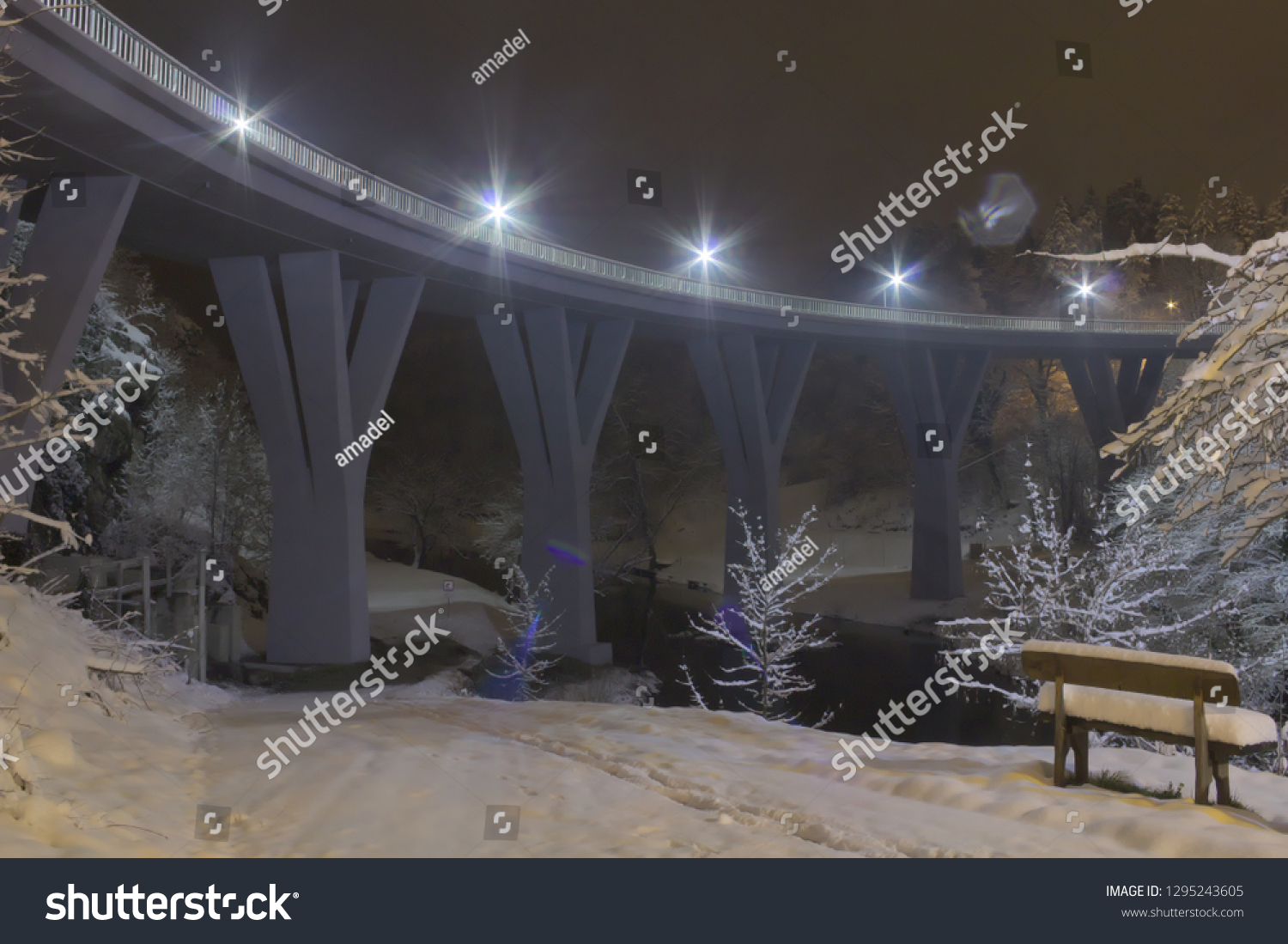 Bench covered in snow. Illuminated bridge in the background. River flowing below the bridge. Snow landscape.