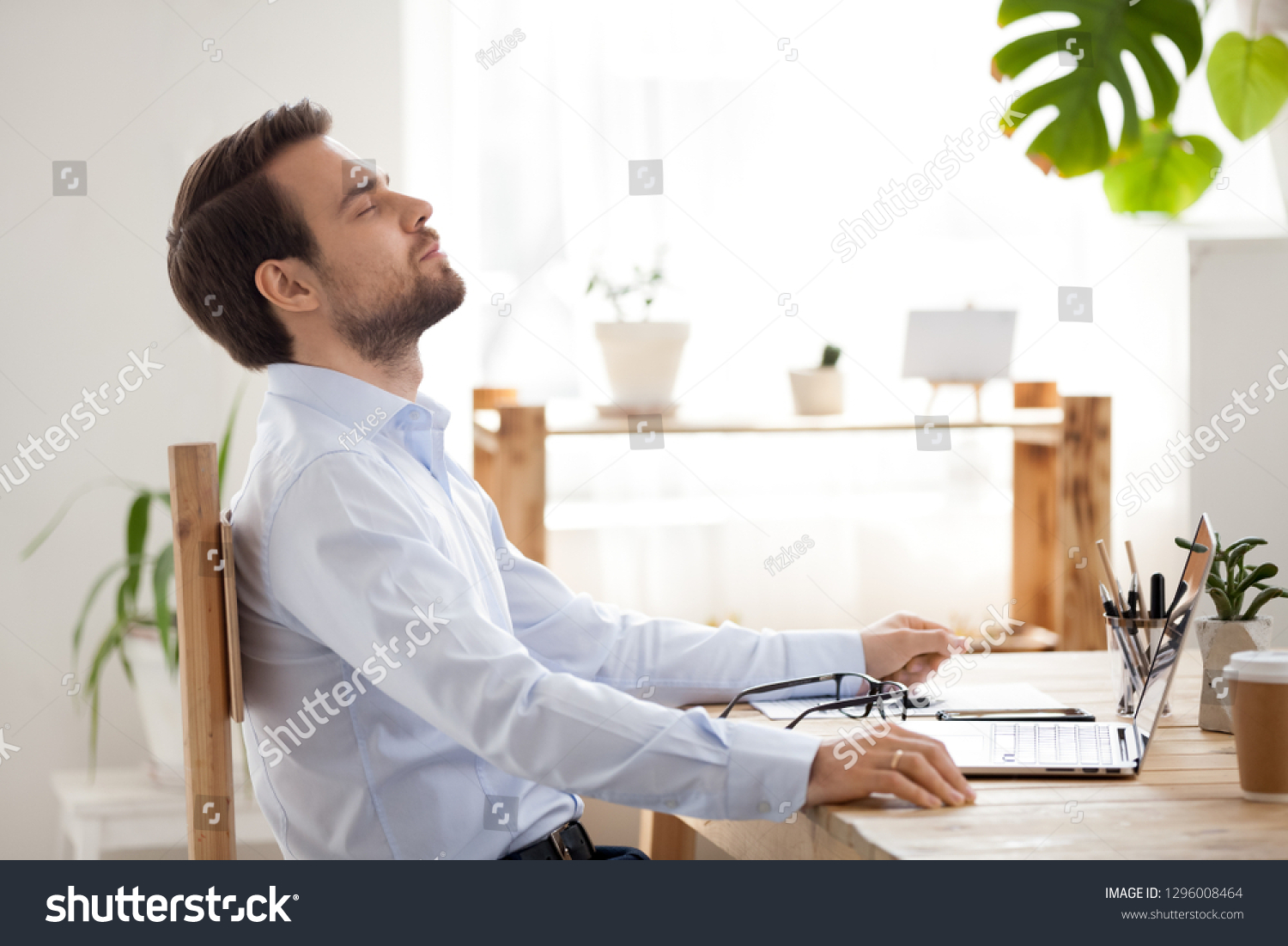 Satisfied calm businessman taking break to relax finished work sitting at desk enjoying stress free job breathing fresh air, happy executive manager resting at workplace dreaming in quiet office #1296008464