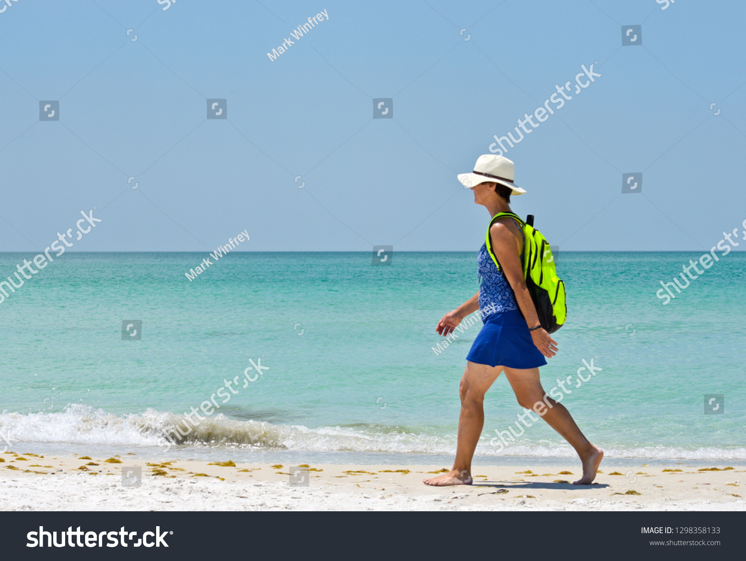 Holmes Beach, Anna Maria Island FL / USA - April 30, 2018: Mature Woman Wearing a Hat with a Backpack Walking on the Beach