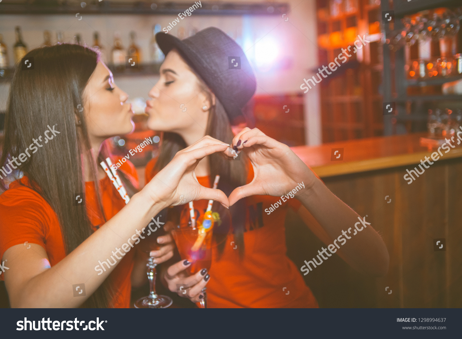 Two young lesbian girls kiss and make a heart with their hands at a club  party