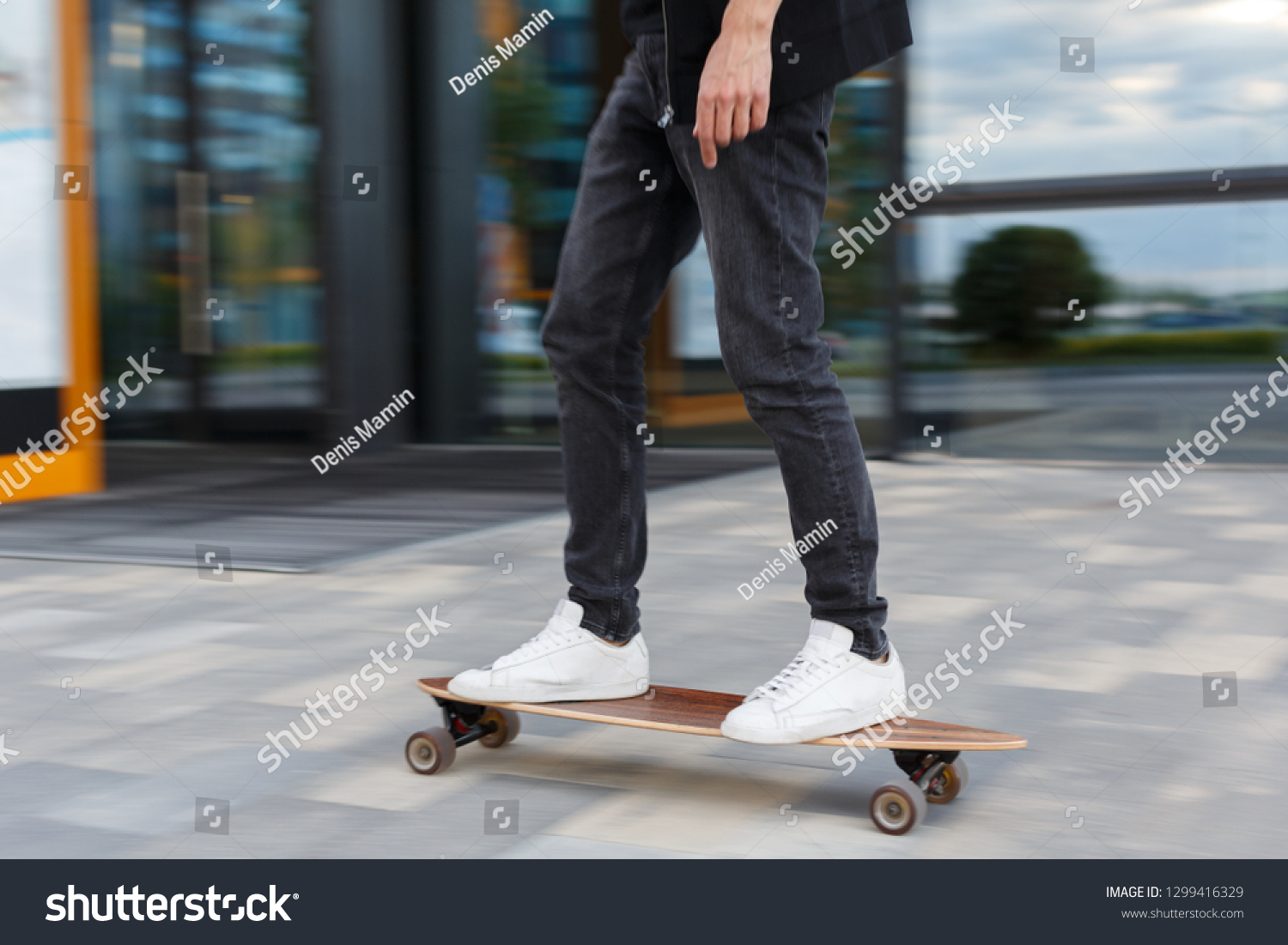 Shot of young man in black jeans and white sneakers riding a longboard in urban area