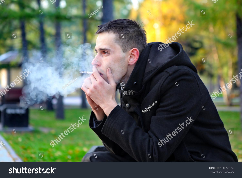 Sad Man Smoking Cigarette In The Autumn Park Stock Photo