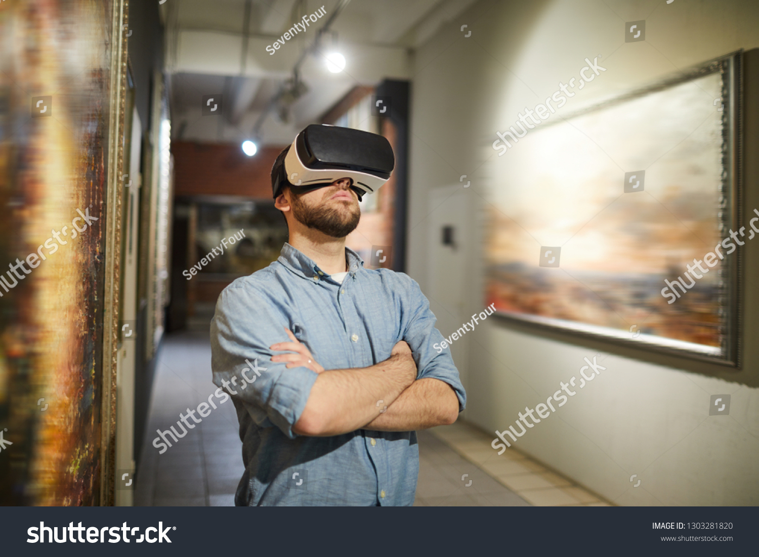 Waist up portrait of modern man wearing VR headset during virtual tour in art gallery or museum, copy space #1303281820