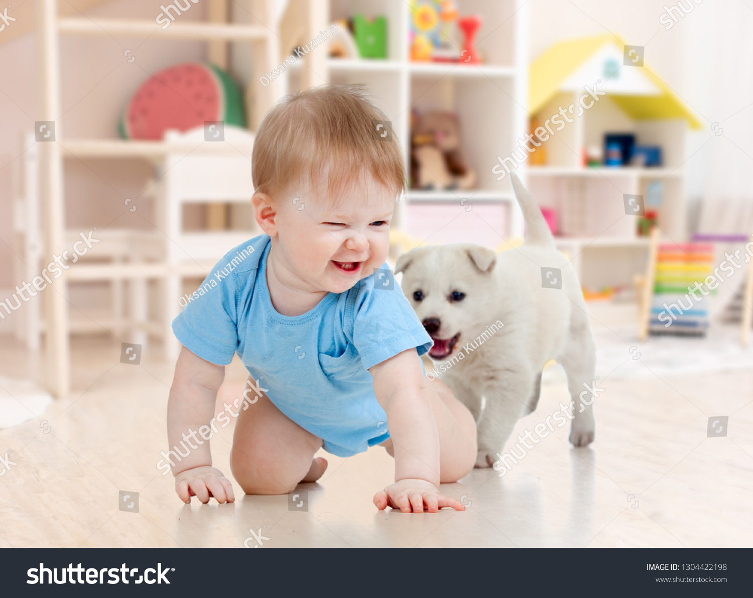 Little baby boy crawling and playing with adorable puppy at home #1304422198