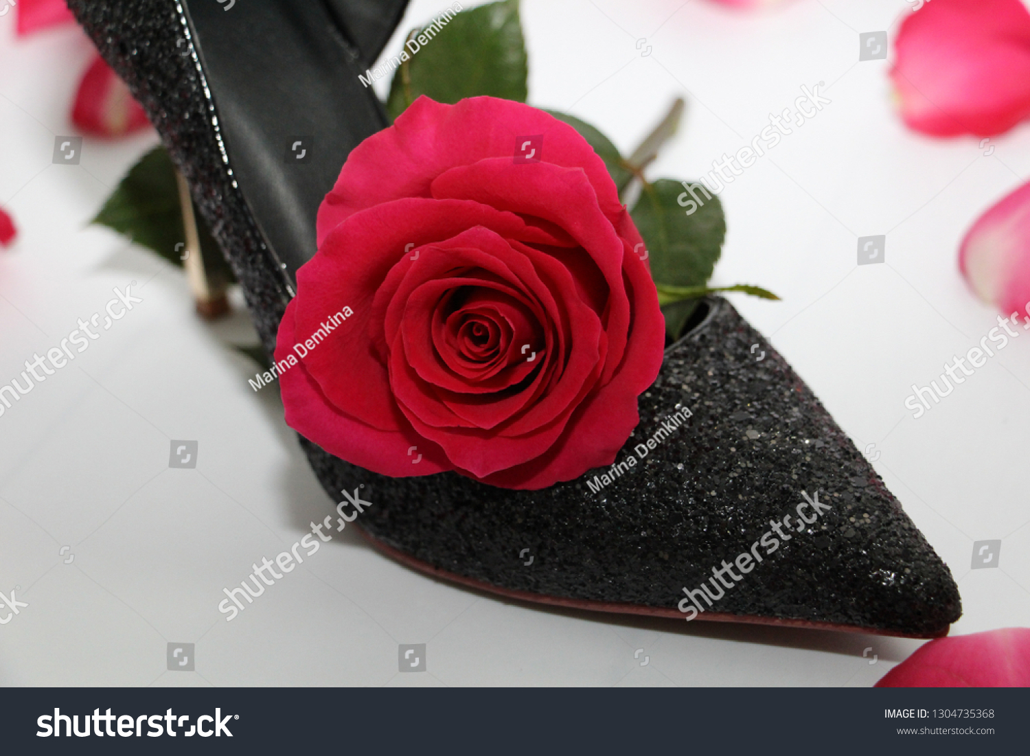 9530d81ae8e Pink rose in a female shoe. Black shoes with high heels. Rose next to.
