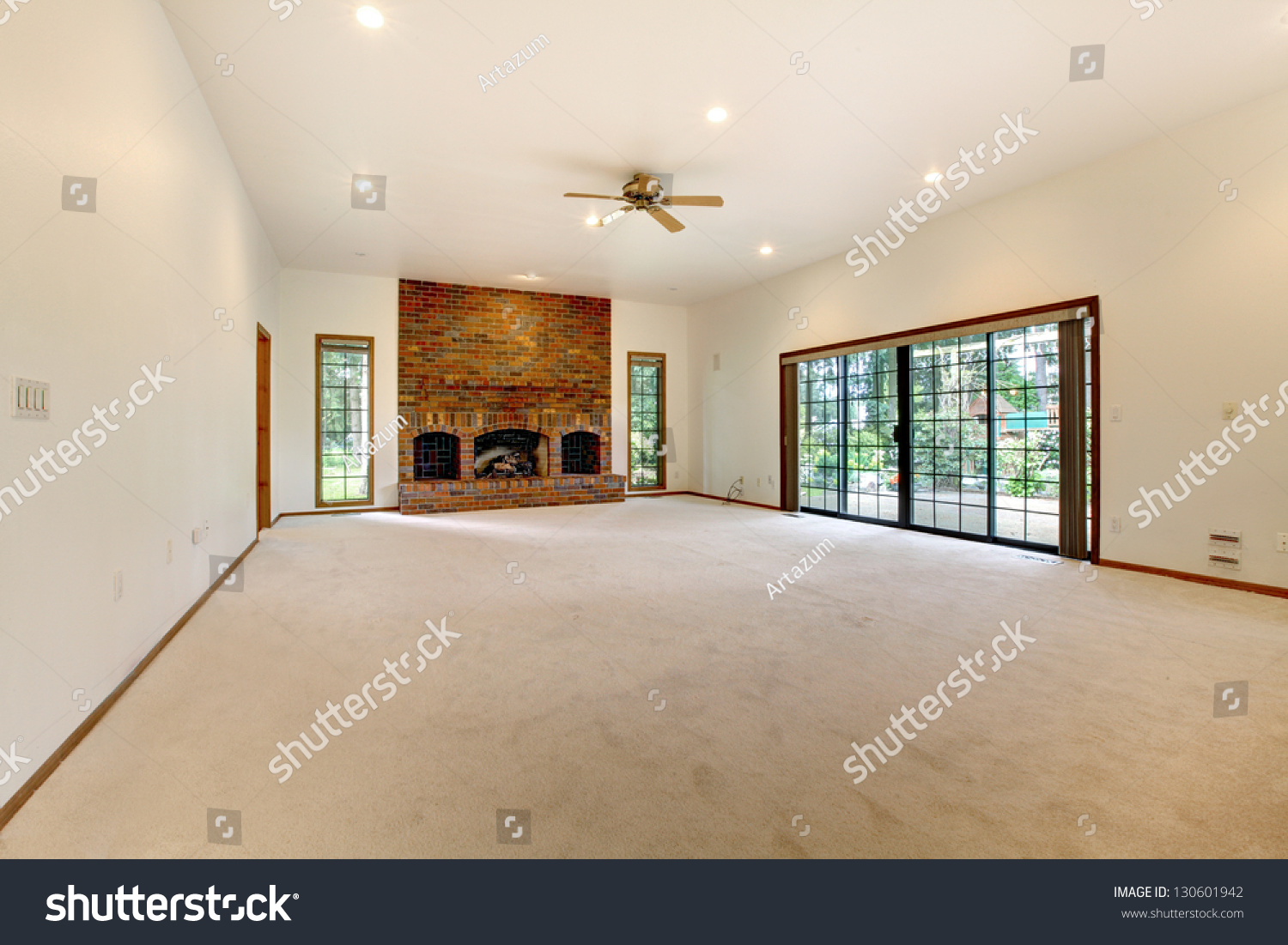 Very Large Empty Living Room With Brick Fireplace And Sliding Doors To The Back Yard