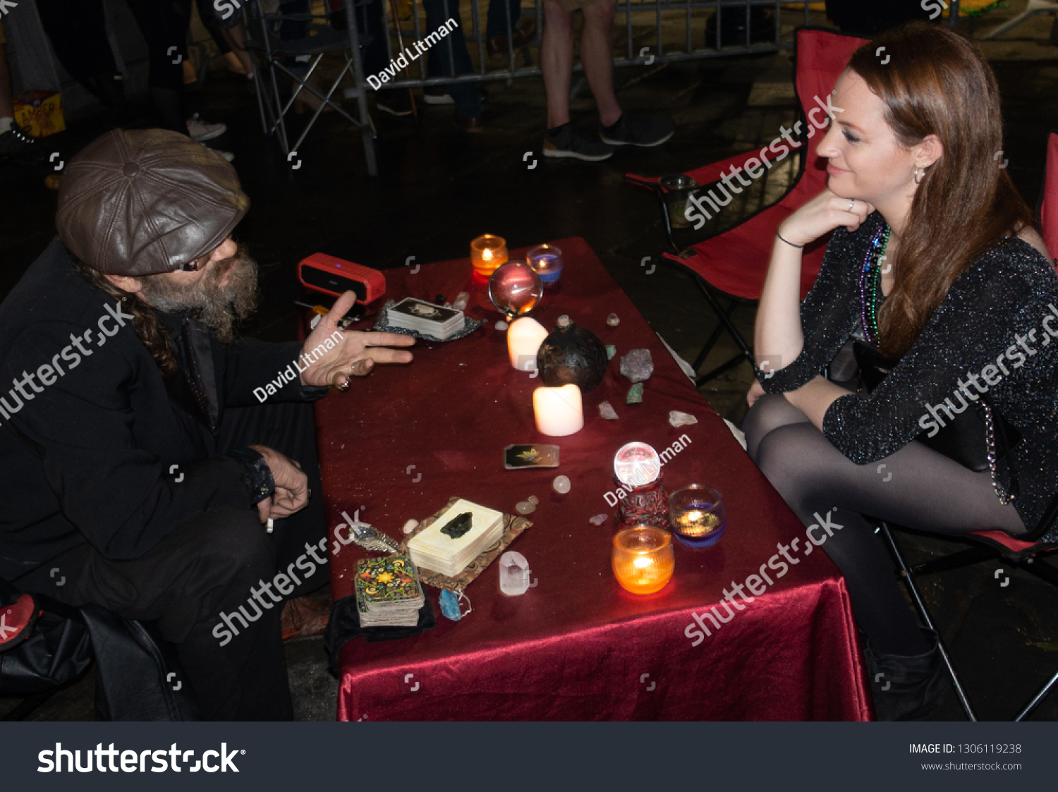 New Orleans, Louisiana - December 31, 2018: A woman gets a psychic tarot card reading from a man with crystal ball, candles, at Jackson Square on new year's eve in the French Quarter of New Orleans.