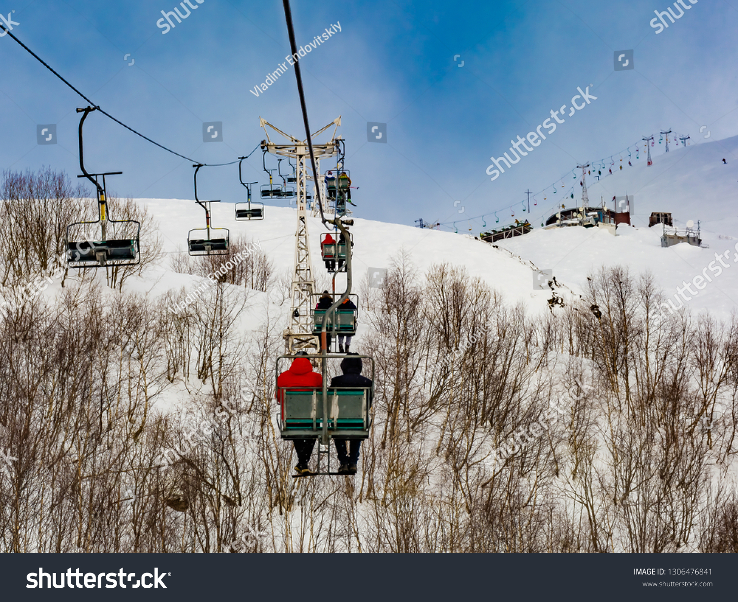Extreme cable car ride. Winter holidays in the mountains. Snow-covered mountain slopes. Skiers and tourists. #1306476841