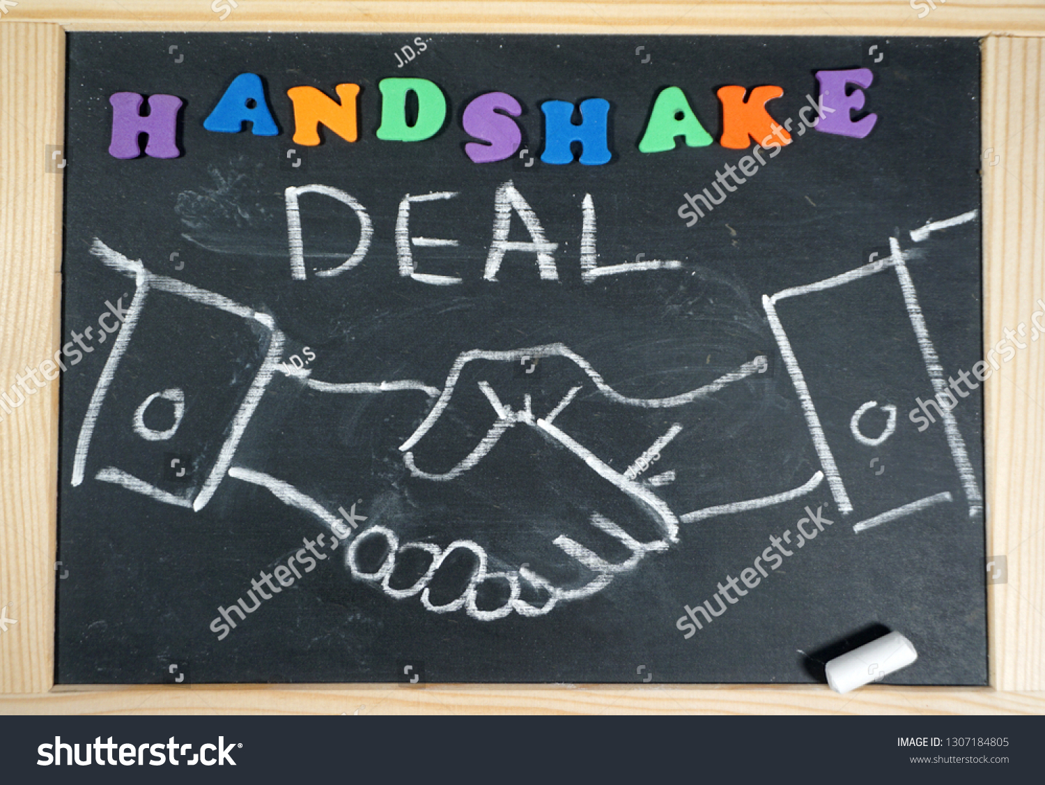 Business handshake on chalkboard with positive message                                #1307184805