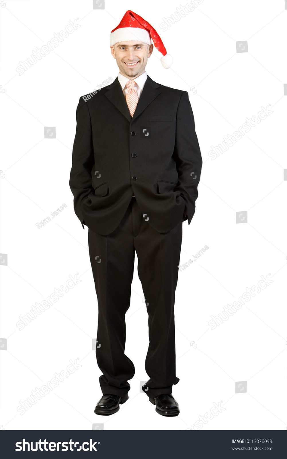 A business man in suit wearing santa claus hat stock