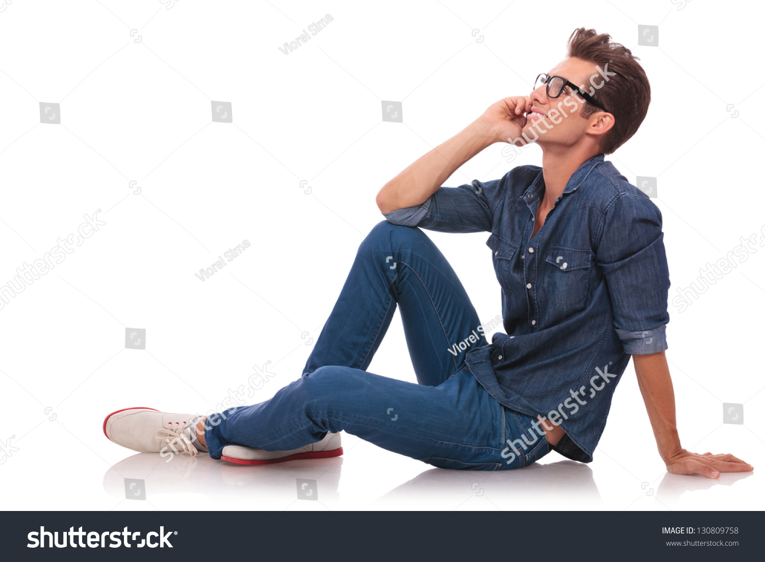 side view casual young man sitting stock photo 130809758 shutterstock. Black Bedroom Furniture Sets. Home Design Ideas