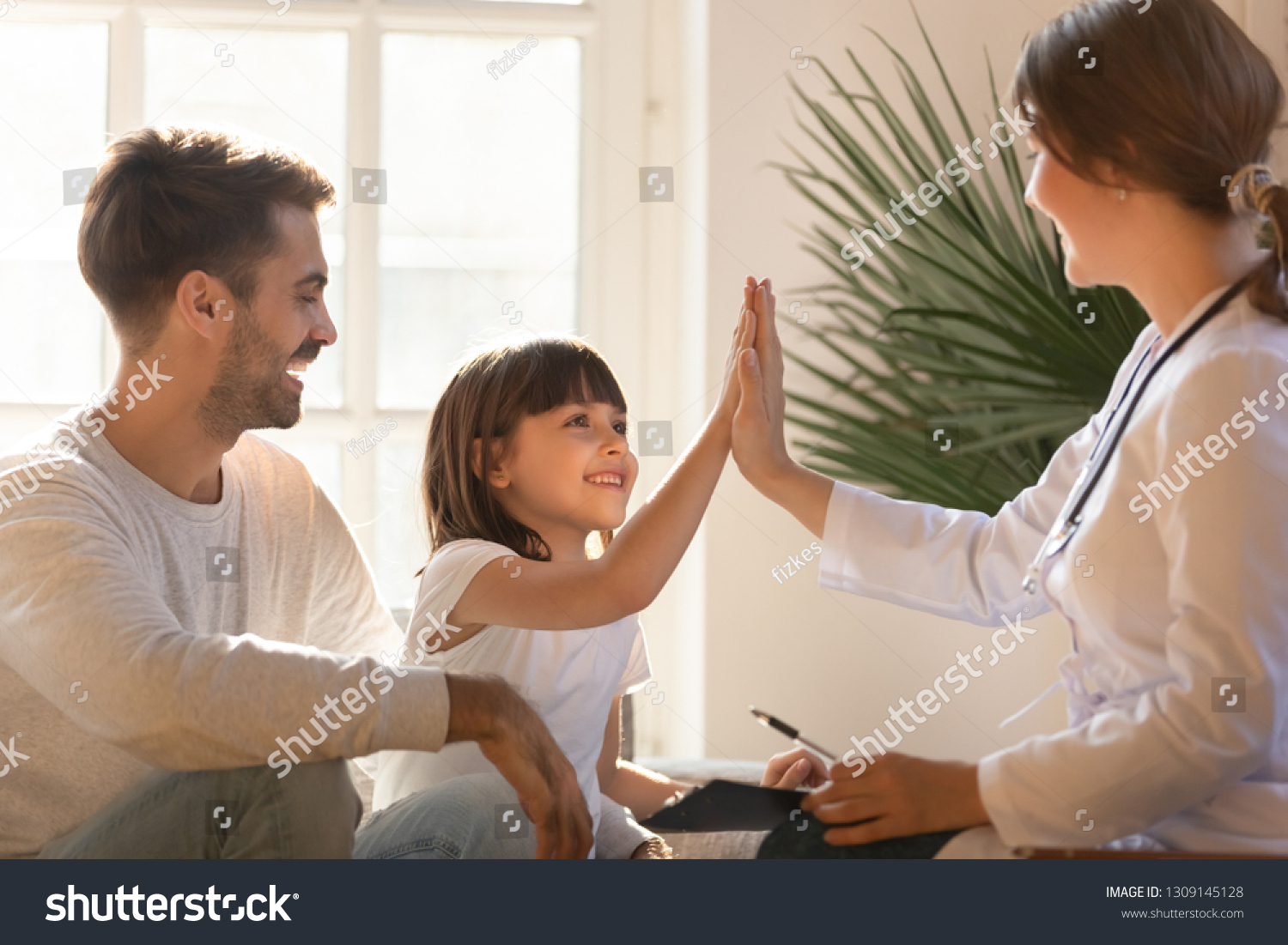Healthy happy child girl giving high five to female caring doctor celebrate good checkup medical result recovery visiting pediatrist in hospital, pediatrician with kid patient good relationship trust #1309145128