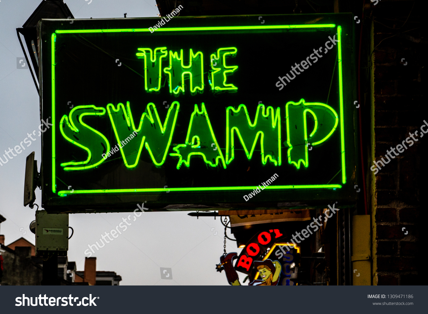 New Orleans, Louisiana - December 30, 2018: The sign marking The Swamp, a buzzing club on Bourbon Street in the French Quarter of New Orleans, serves food and drinks with live music and sports bar.
