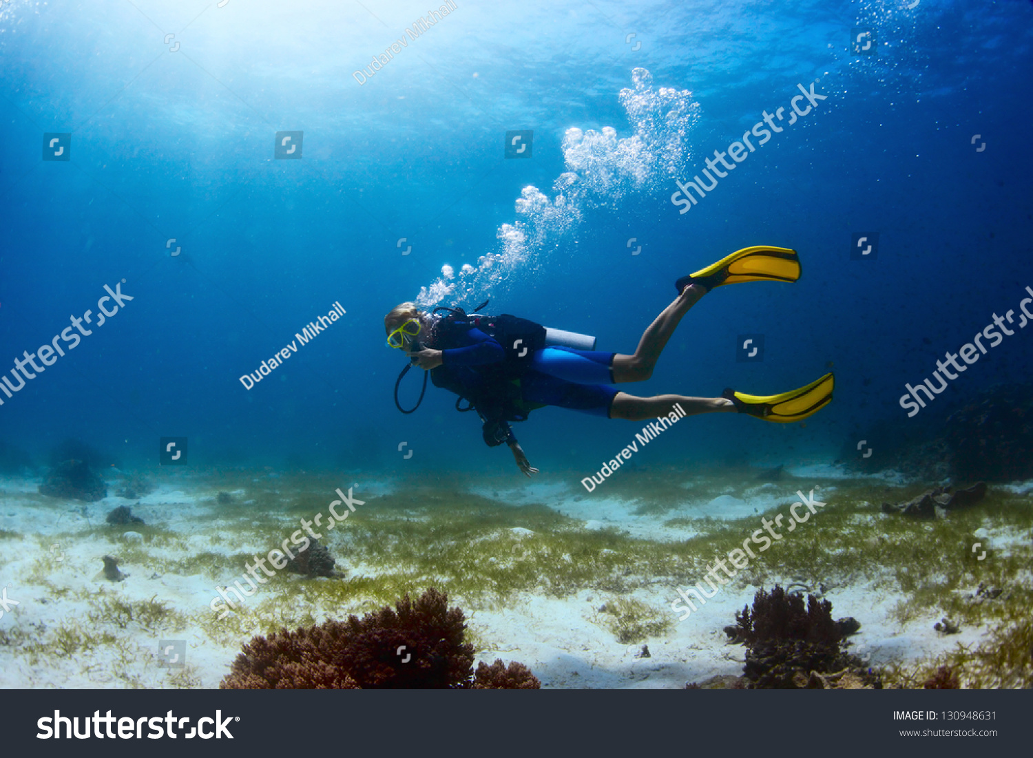 Scuba diver exploring tropical dive site and finning over bottom #130948631