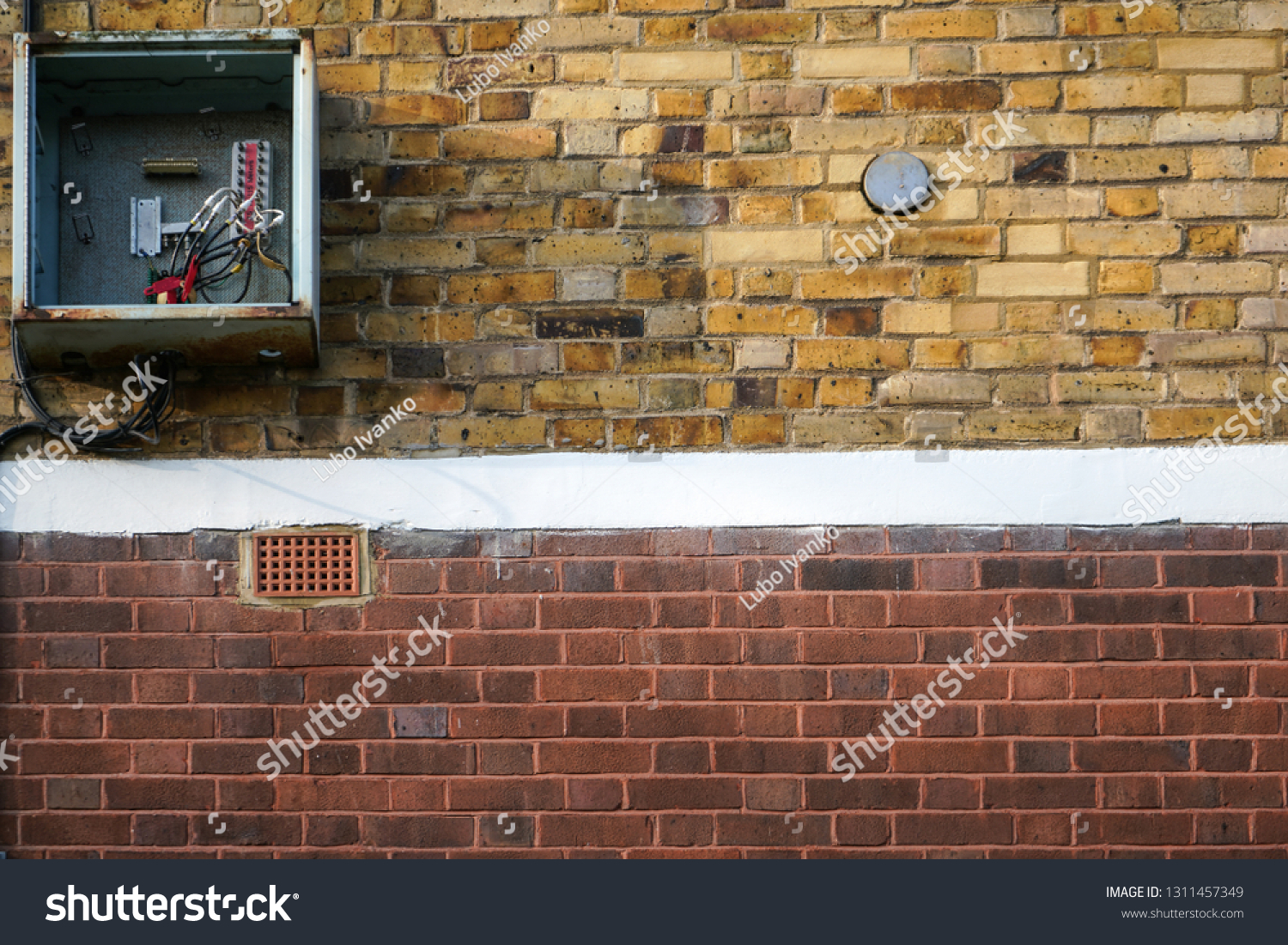 bricks wall, with electricity fuse box on it, opened, cover missing, cables