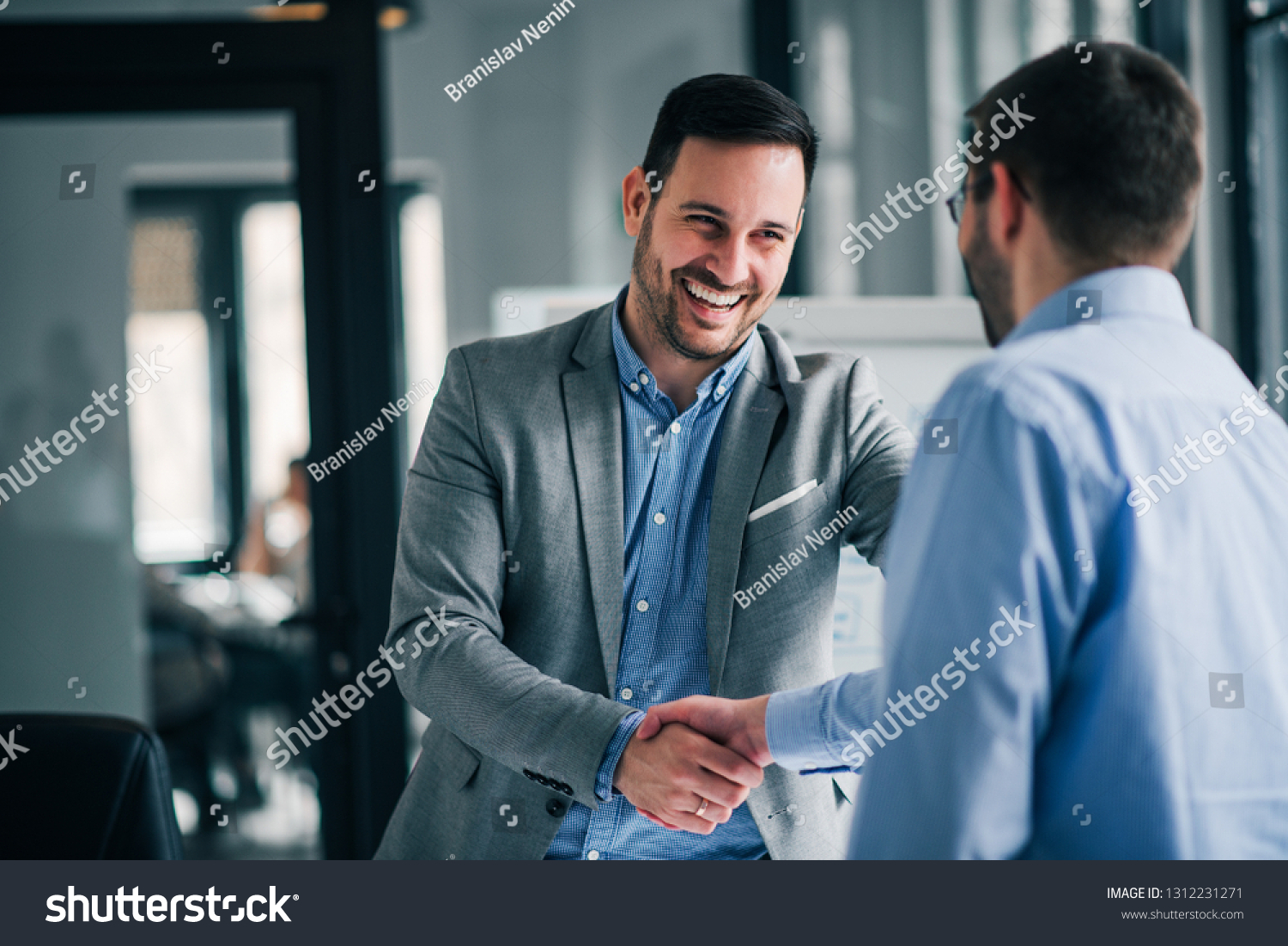 Portrait of cheerful young manager handshake with new employee.  #1312231271