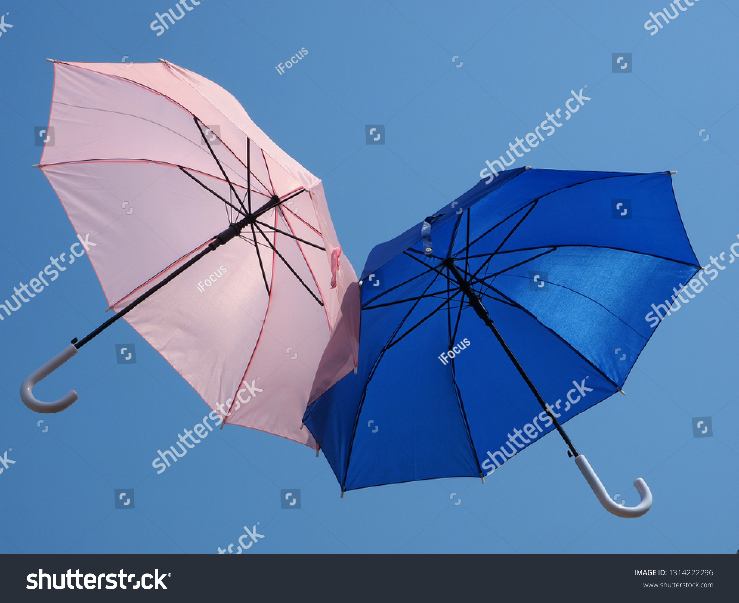 Pink and blue umbrellas fly in blue sky