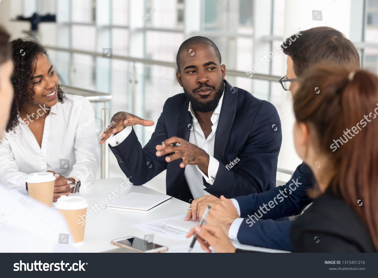 Millennial employees gathered in boardroom for training, black boss ceo leader leading corporate team during seminar learning at modern office. Internship and leadership coaching and education concept #1315451216