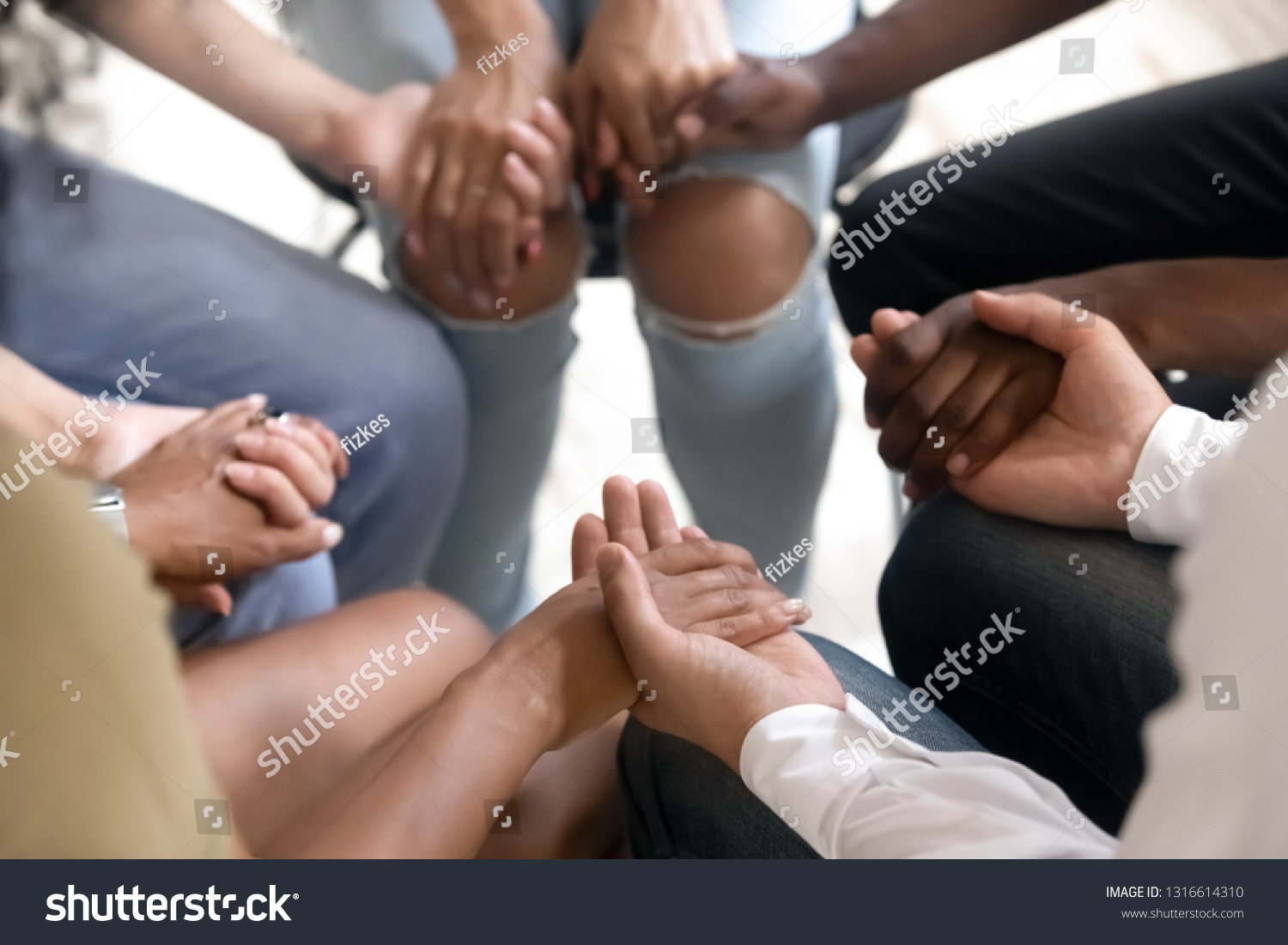 Diverse people sitting in circle holding hands at group therapy session, religious christian team pray together for recovery give psychological support, counseling training trust concept, close up #1316614310