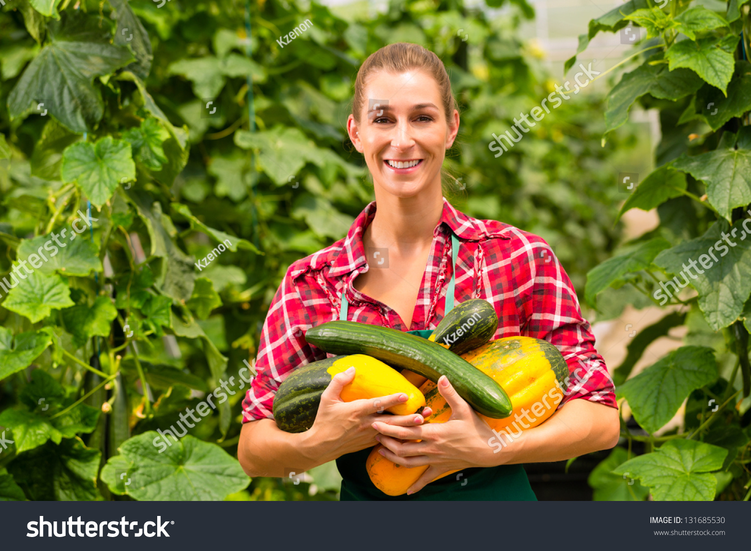 Female Gardener At Market Gardening Or Nursery With Apron And Vegetables