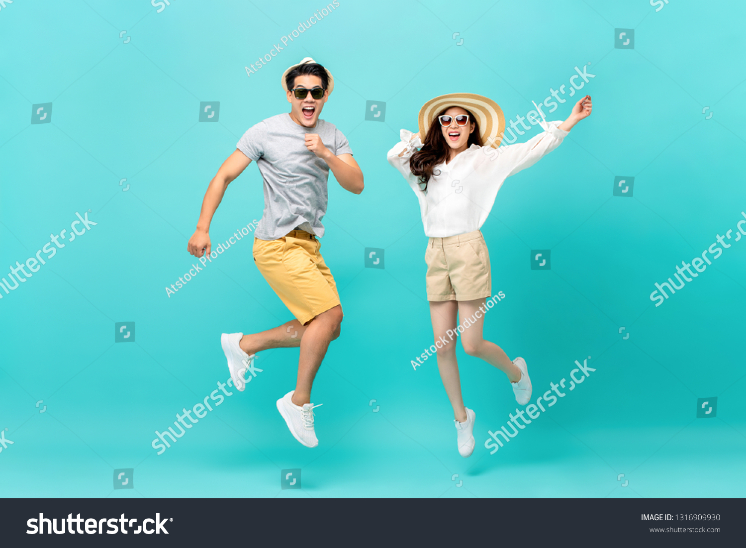 Playful energetic Asian couple in summer beach casual clothes jumping isolated on light blue background studio shot #1316909930
