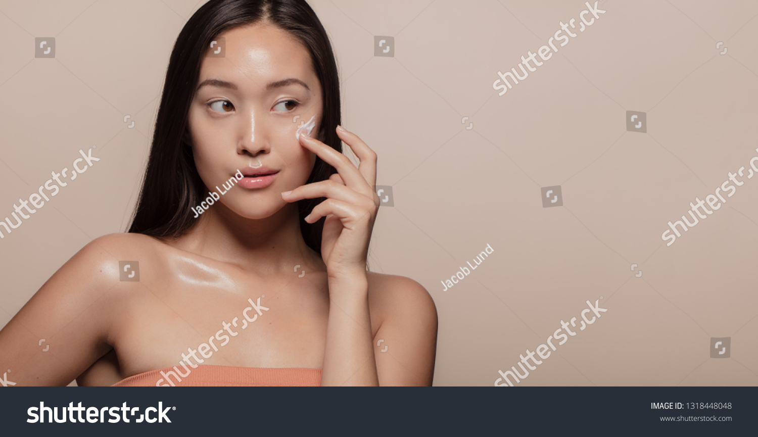 Young Korean woman applying moisturizer to her face over beige background. Young woman with cosmetic cream on a cheek and looking away. #1318448048