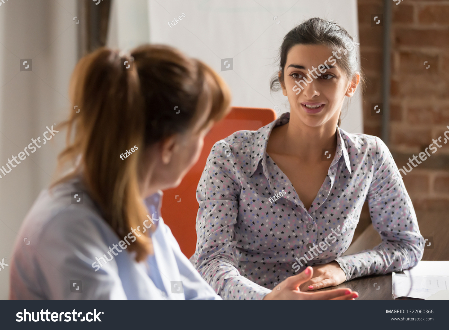 Indian businesswoman speaking to colleague or hr during job interview, young professional hindu woman manager consulting client or explaining giving advice teaching at business office meeting #1322060366