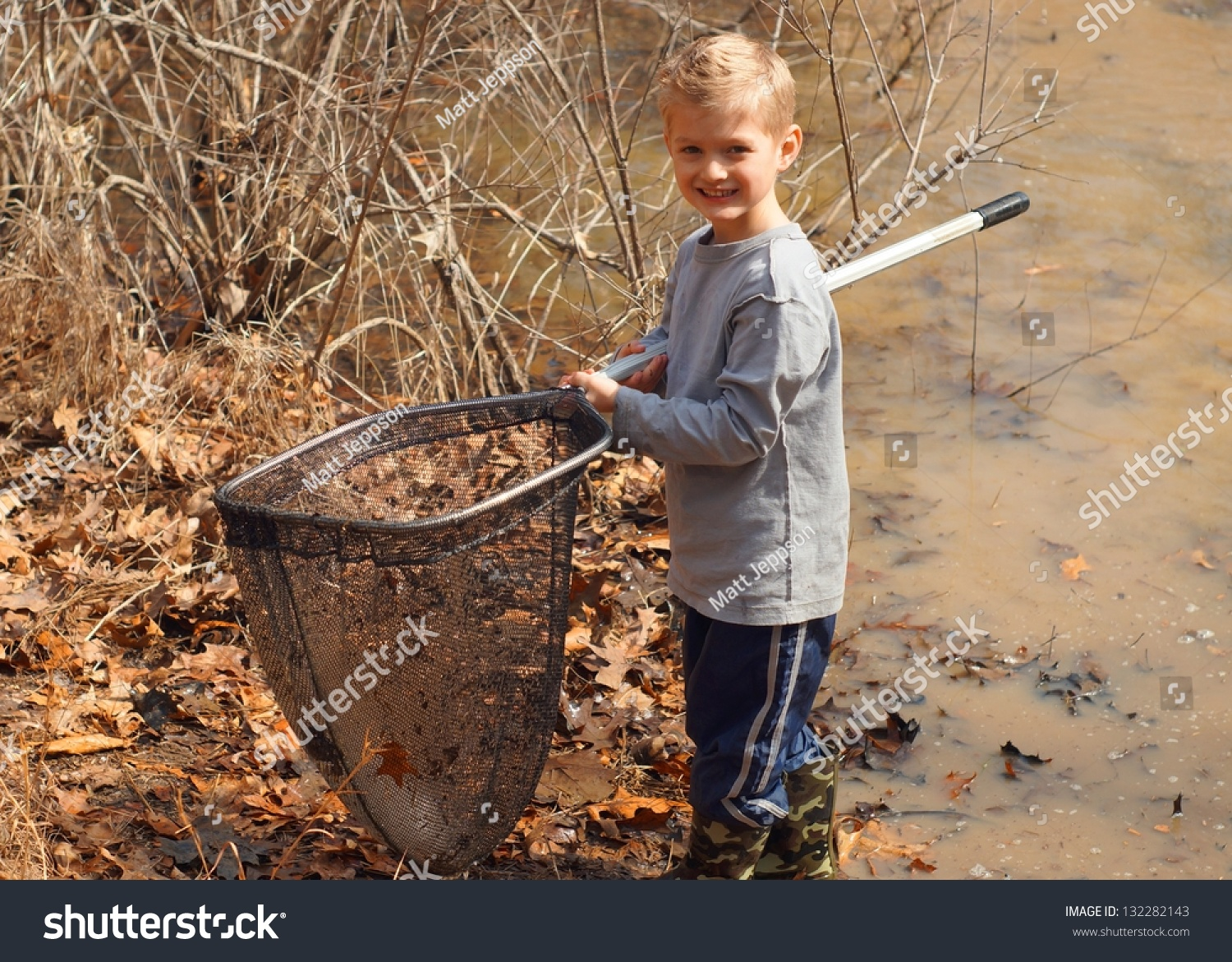 Boy using net catch tadpoles fish stock photo 132282143 for Fish catching net