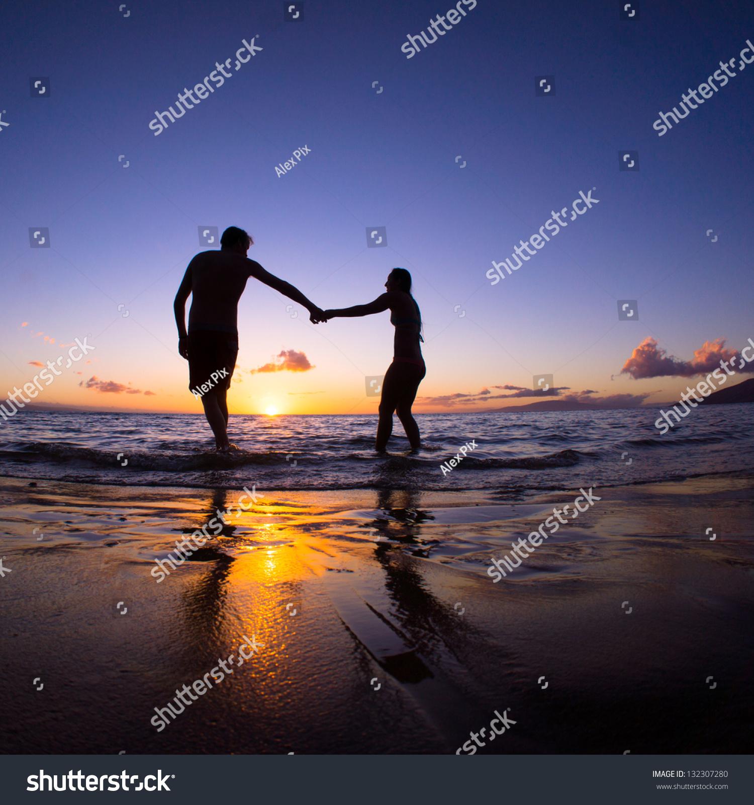 Romantic Couple Enjoying A Beach Walk At Sunset Stock