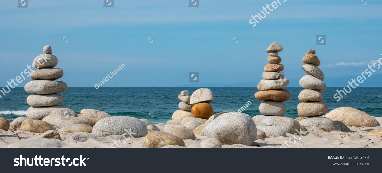 Zen stone towers are piled high on a mostly sunny day along the Pacific Coast of central California at Spanish Bay Beach,  on the famous 17 mile drive, next to Asilomar State Park.