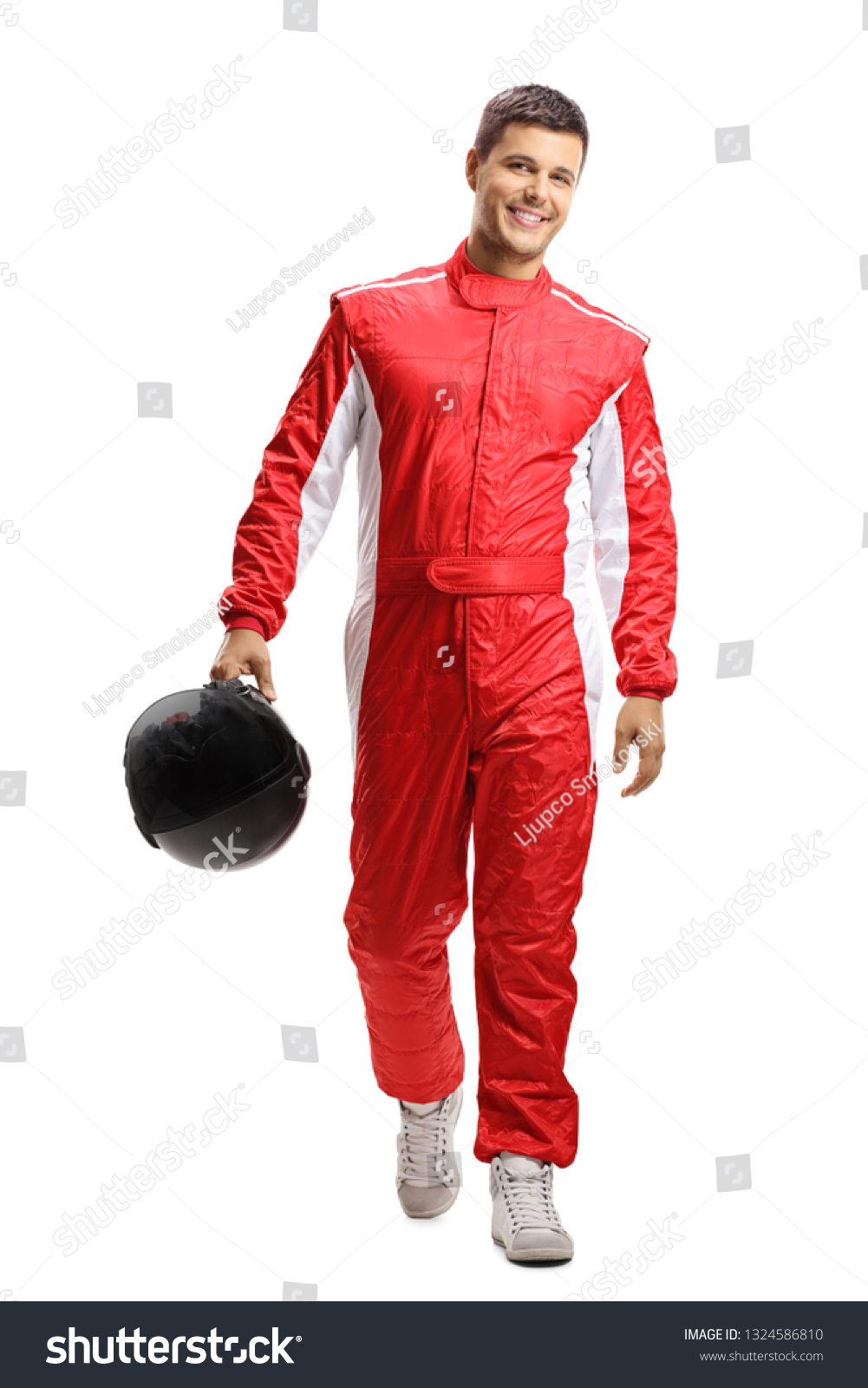 Full length portrait of a male car racer holding a helmet and walking towards the camera isolated on white background #1324586810