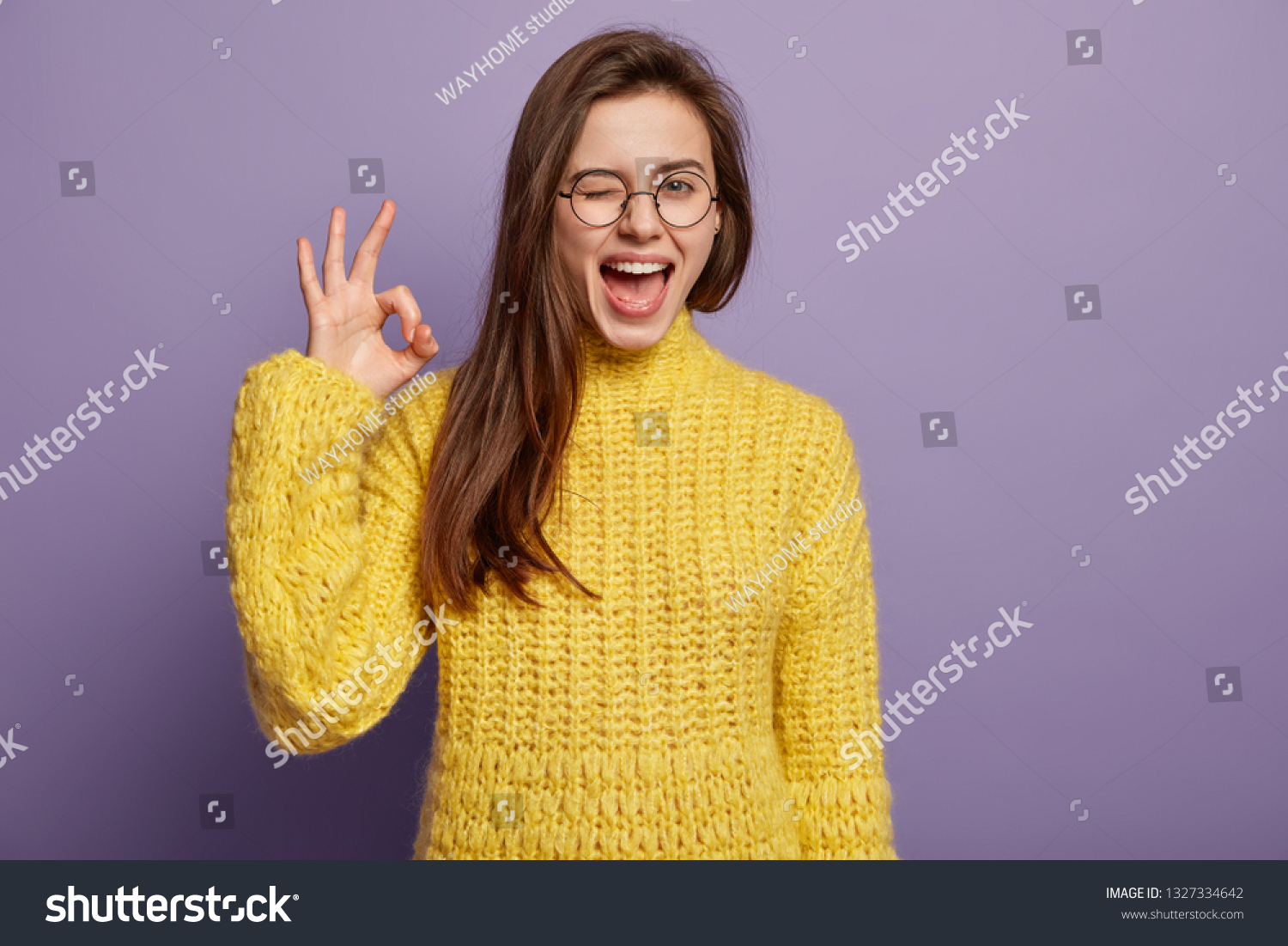 Waist up shot of pleased young woman says good job or well done, makes okay gesture, demonstrates symbol of approval and like, blinks eye, wears spectacles, knitted yellow jumper, stands indoor #1327334642