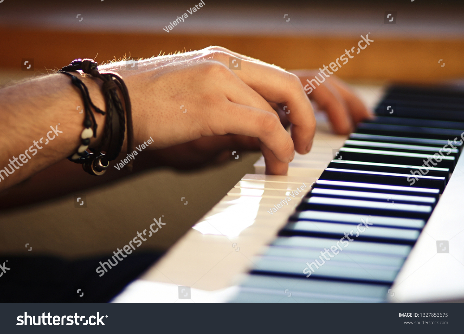 On the keyboard instrument, which is illuminated by weak sunlight, men's hands press the keys, playing a melody #1327853675