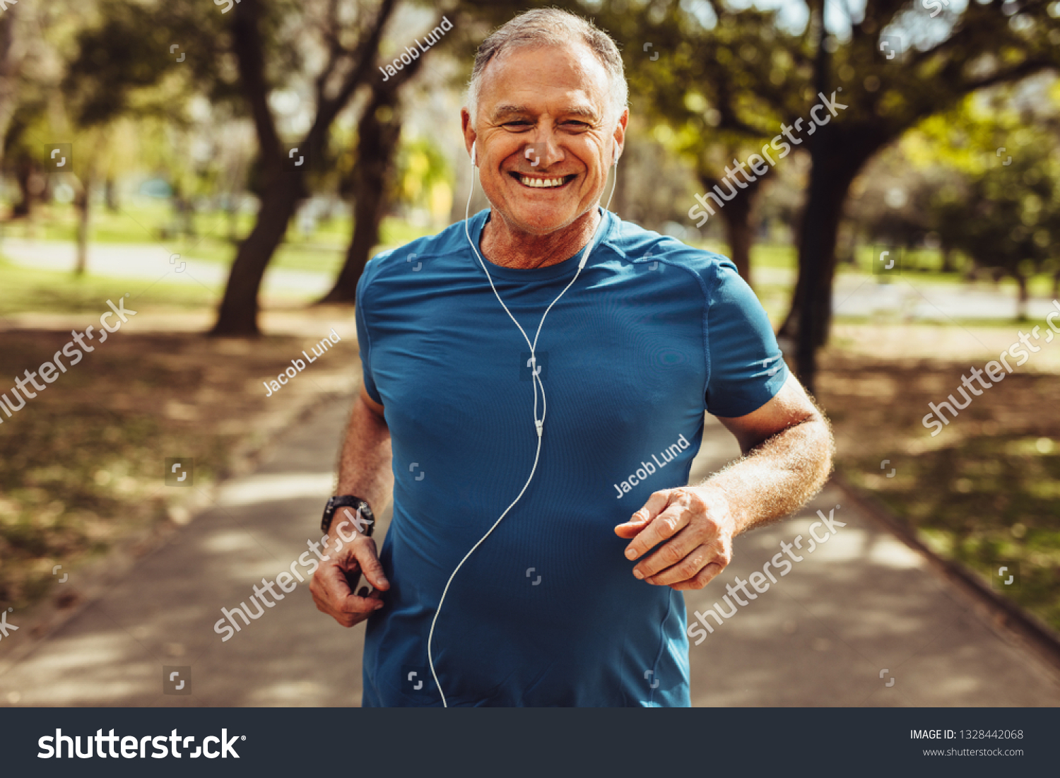 Portrait of a senior man in fitness wear running in a park. Close up of a smiling man running while listening to music using earphones. #1328442068