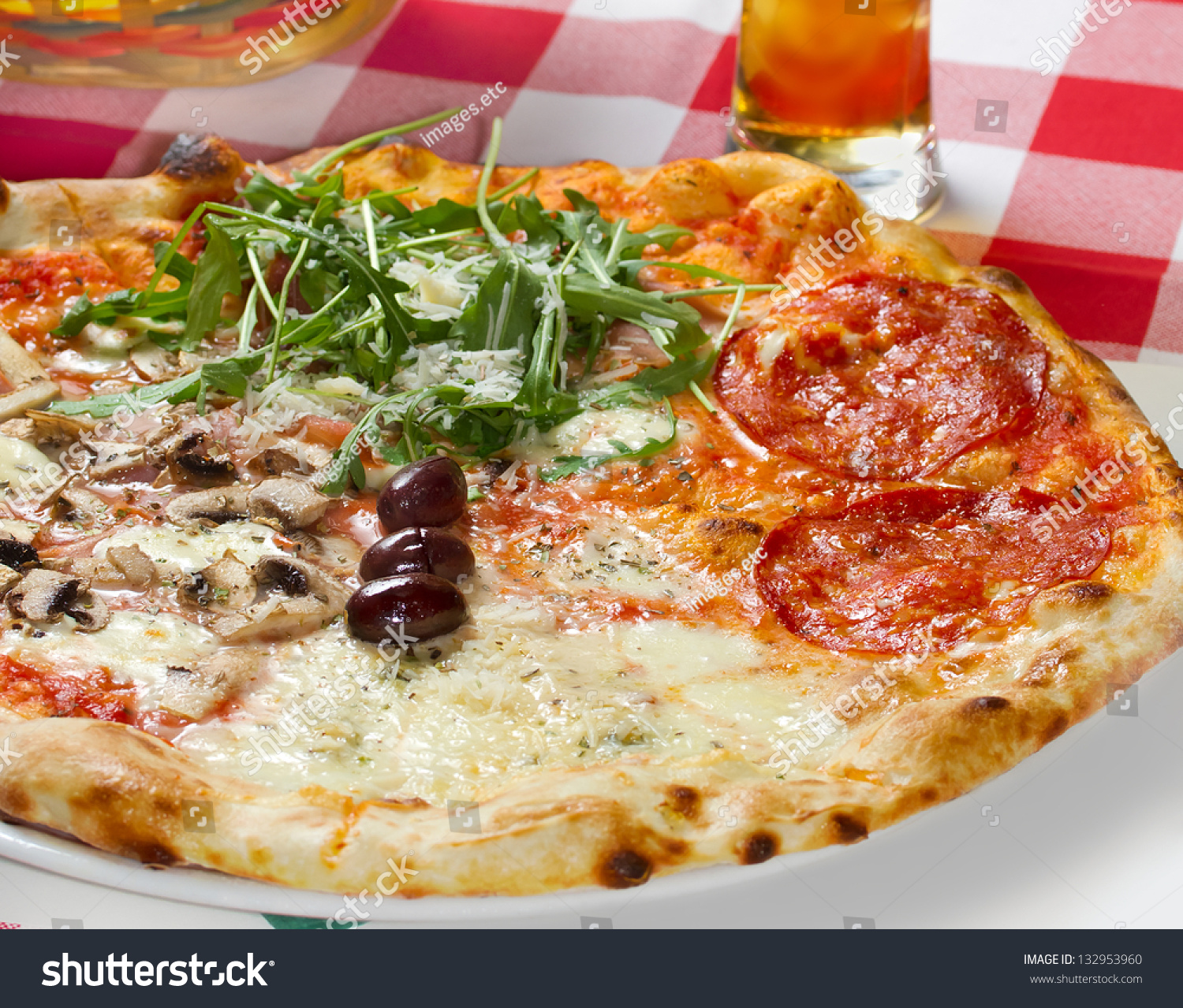 Quattro Stagioni (four Seasons) Pizza On A Restaurant Table. Studio Shot