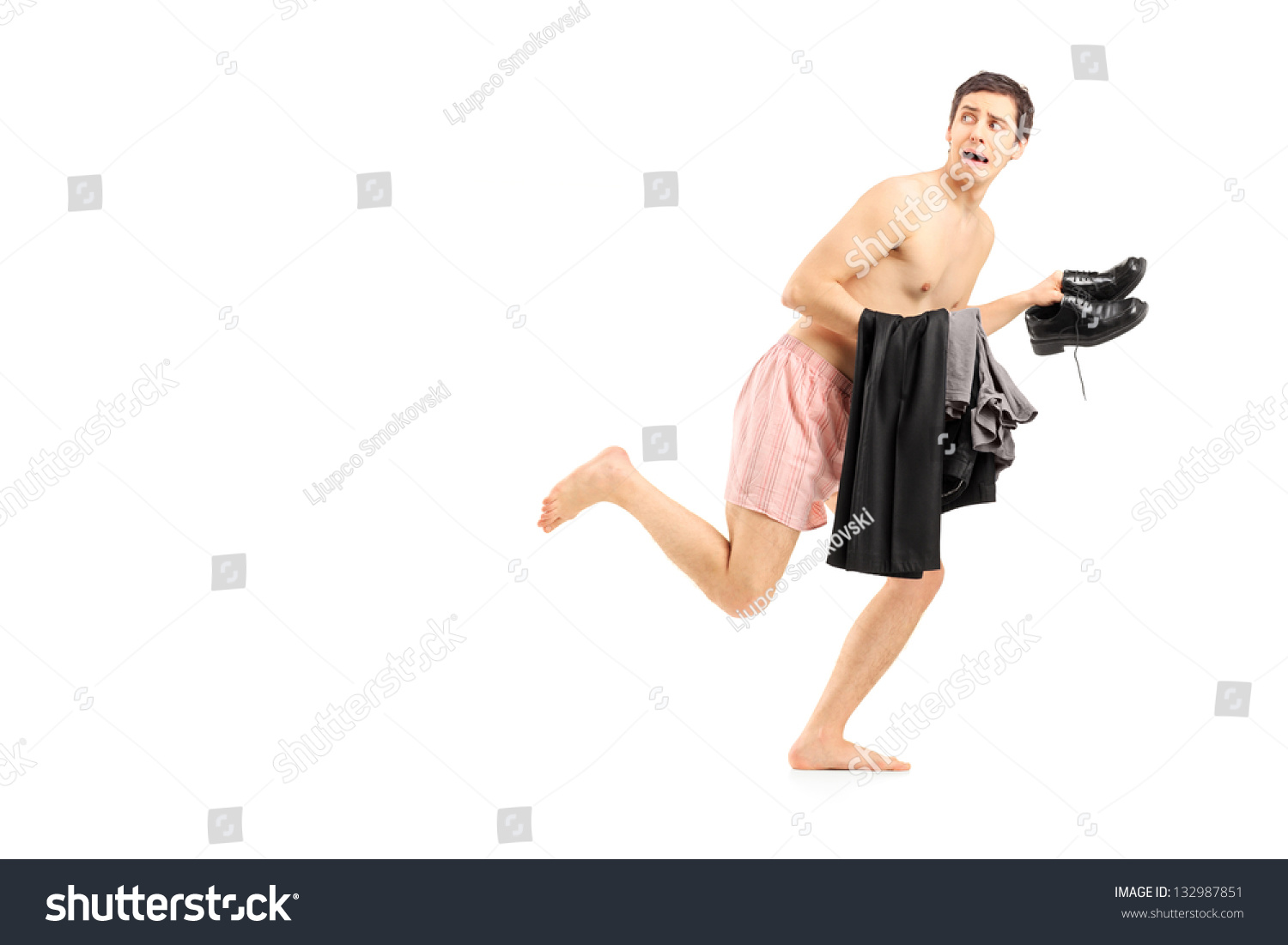 An Embarrassed Naked Man In Underwear Holding His Clothes
