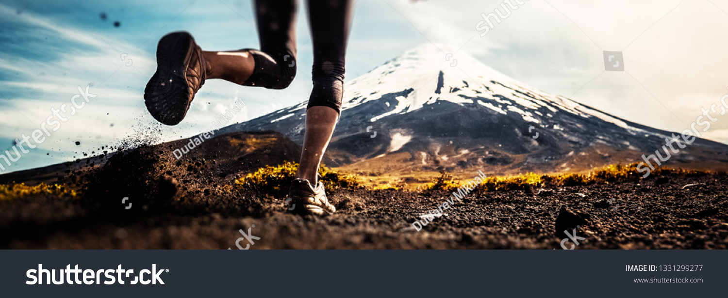 Legs of the woman running on the trail with volcano on the background #1331299277