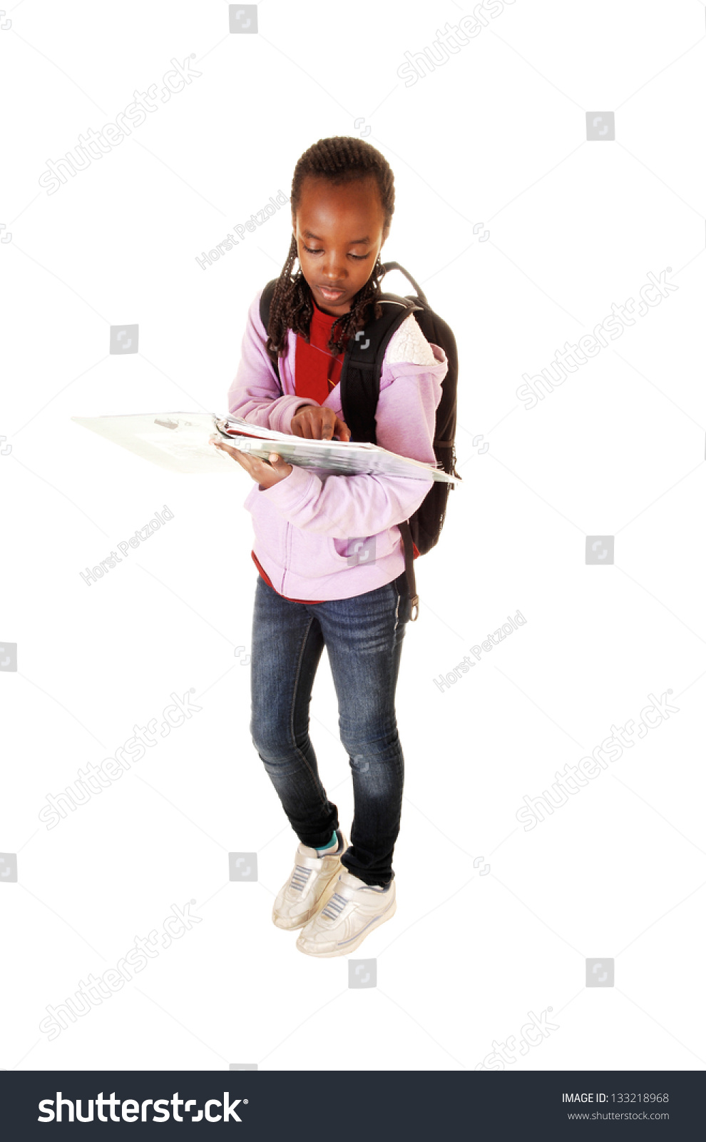 A young black teen girl standing for white background with her backpack on  her back,