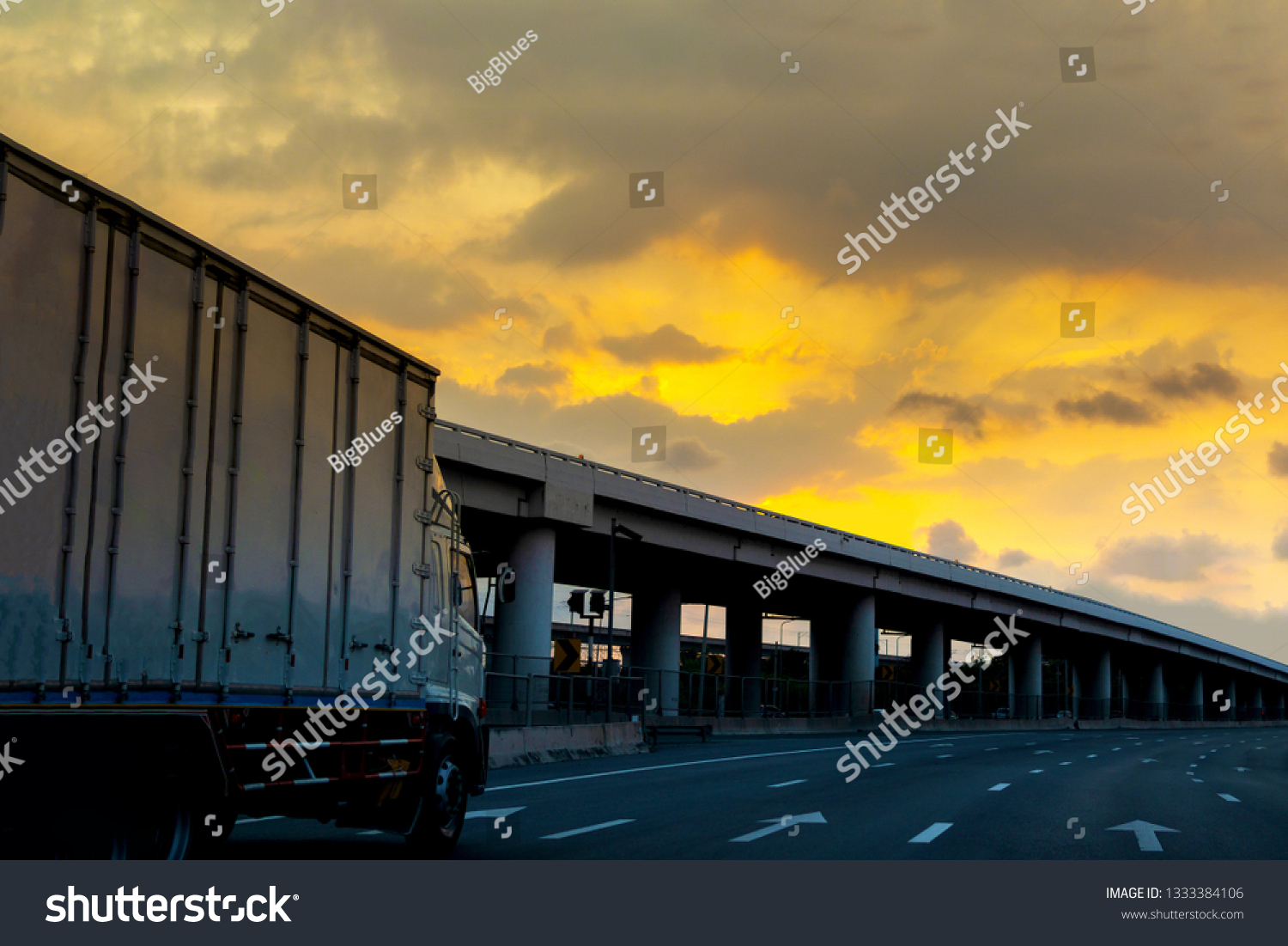 Truck on highway road with container, transportation concept.,import,export logistic industrial Transporting Land transport on asphalt expressway with sunrise sky #1333384106