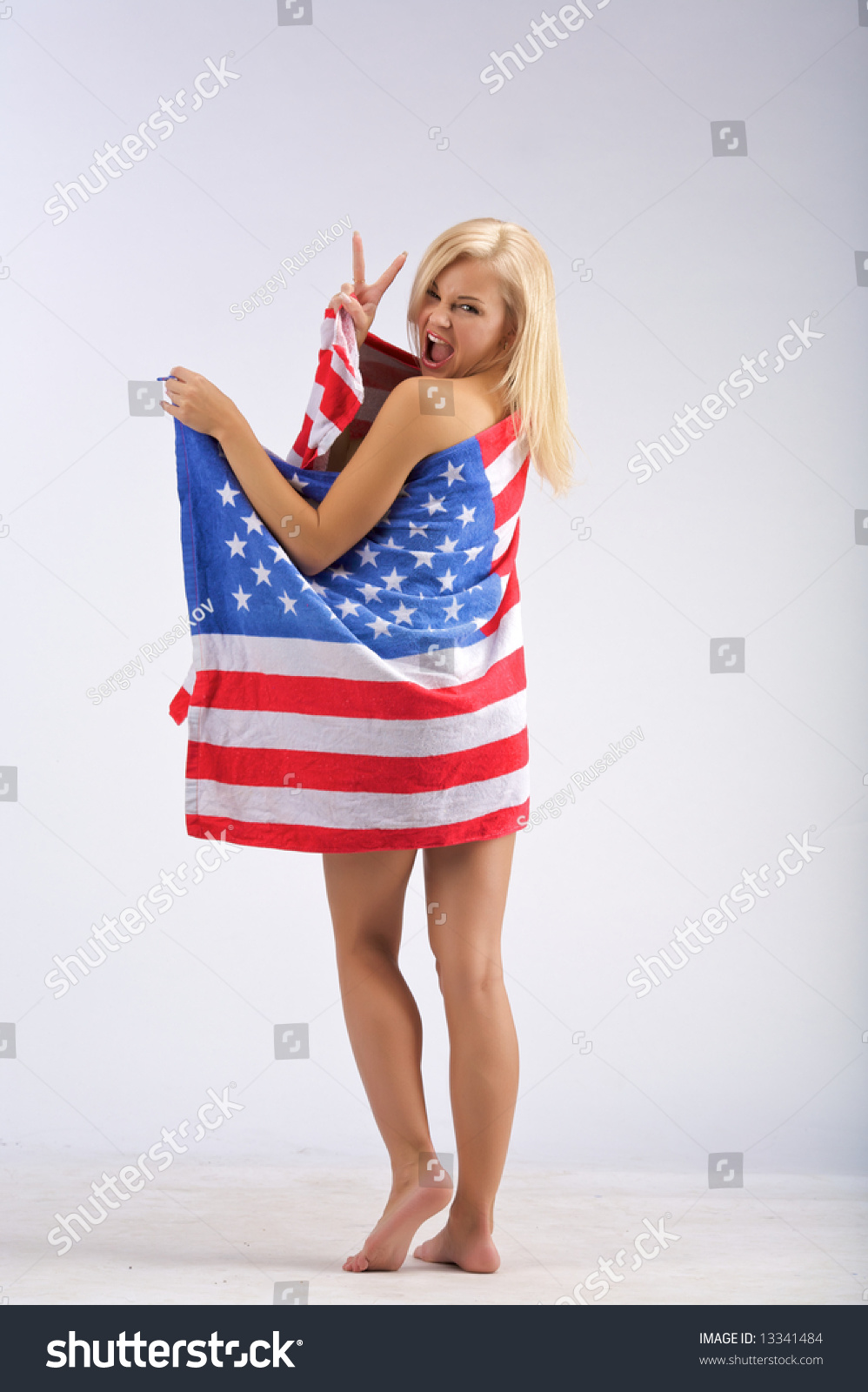 Naked Girl In The American Flag Stands And Shows Victory