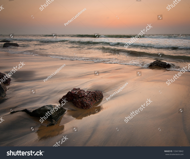 Sunset At Tropical Beach. Rocks At The Ocean Coast Under