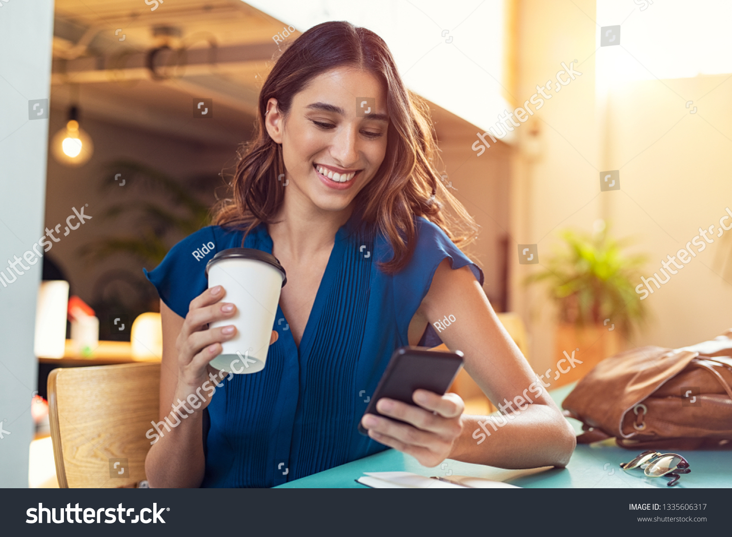 Young beautiful woman holding coffee paper cup and looking at smartphone while sitting at cafeteria. Happy university student girl using mobile phone. Businesswoman drinking coffee and smiling. #1335606317