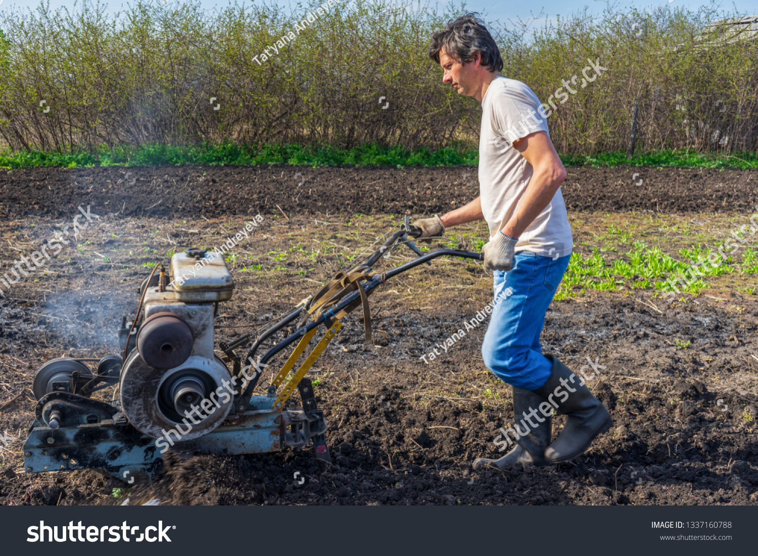 Man in wellingtons with cultivator ploughs ground in sunny day. Land cultivation, soil tillage. Spring work in garden. Gardening concept #1337160788