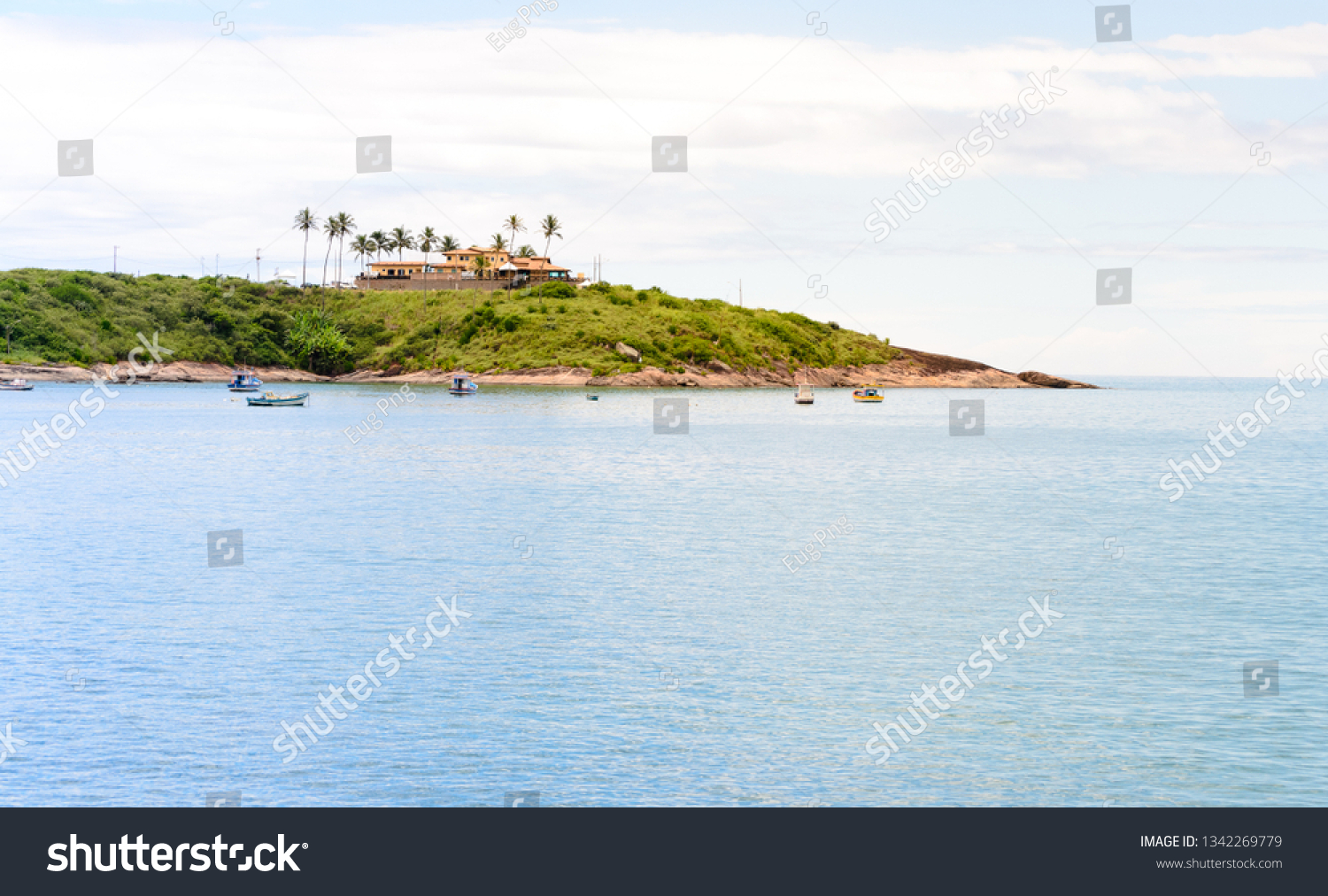 A lovely bay with some little boats and a  sand beach in Meaìpe a small fishing village near Guarapari in the Espirito Santo state in Brazil #1342269779