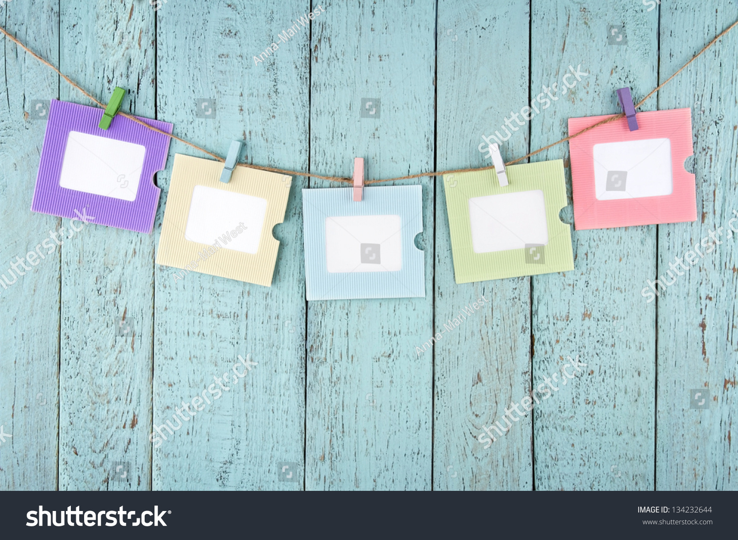 five empty colorful photo frames or notes paper hanging with clothespins on wooden blue vintage shabby