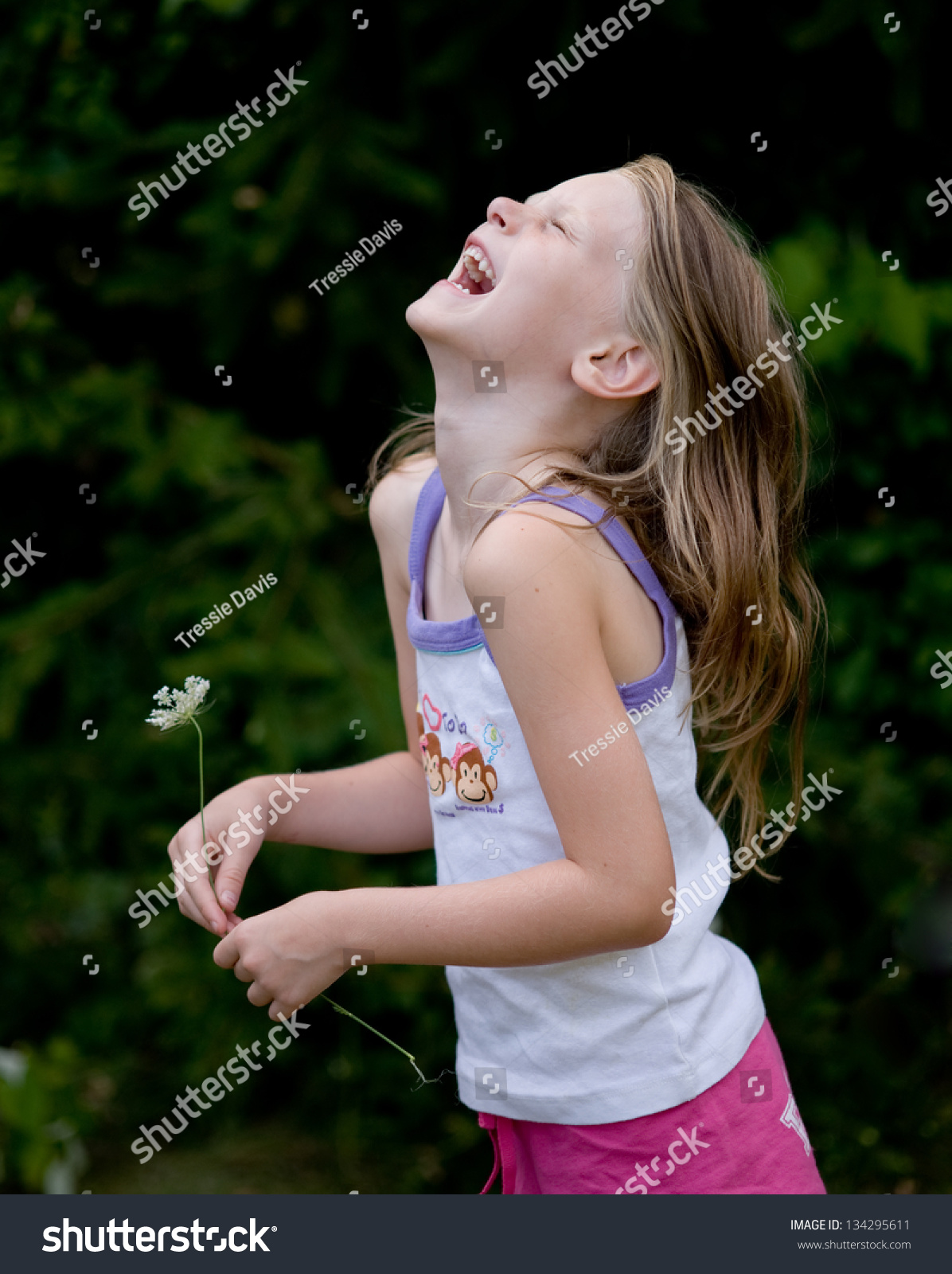 320e2b8e9098a Little girl wearing shorts and tank top holding queen annes lace laughing  joyfully