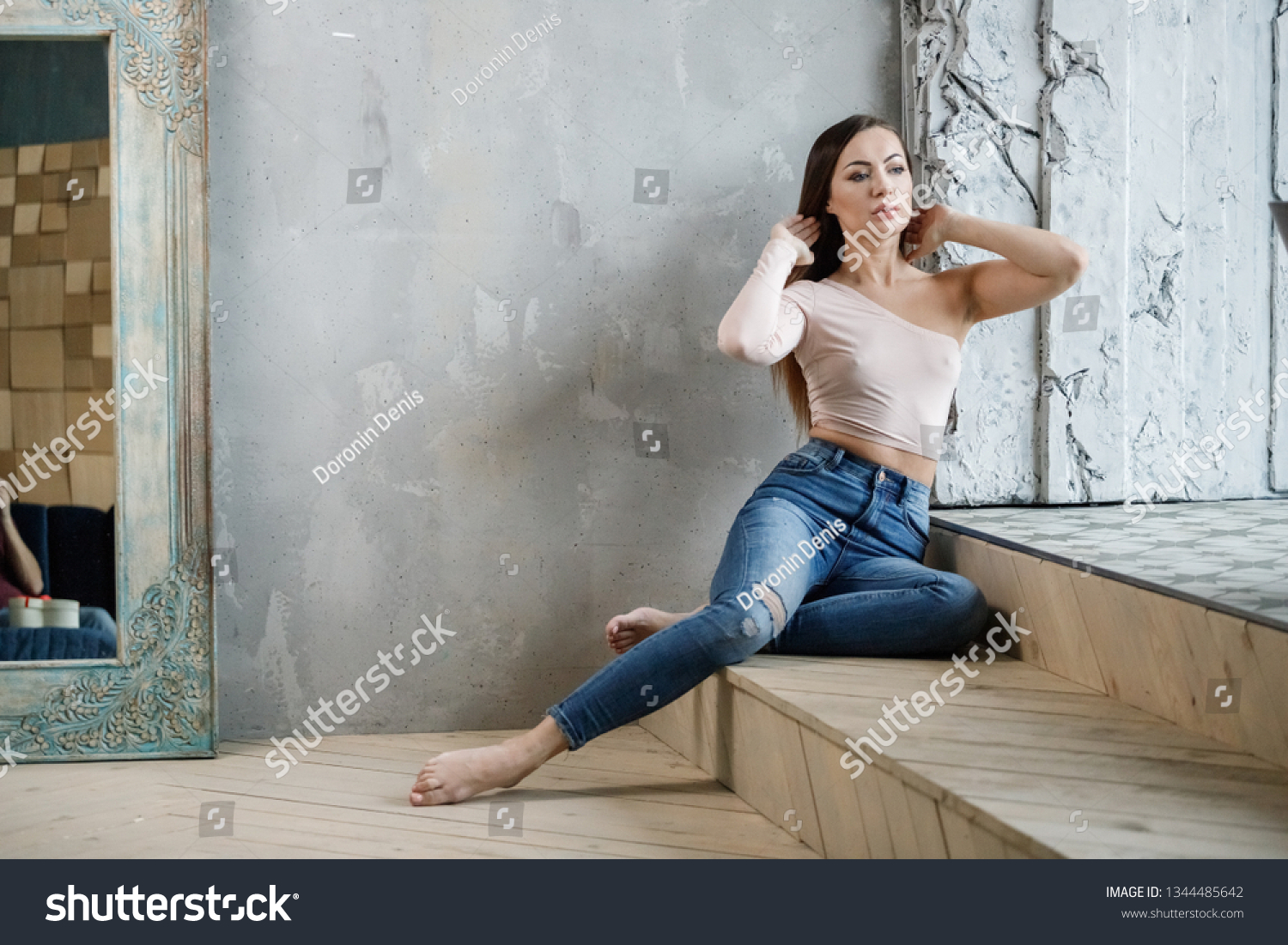 https://image.shutterstock.com/shutterstock/photos/1344485642/display_1500/stock-photo-beautiful-girl-sexy-brunette-in-jeans-and-t-shirt-posing-in-a-room-in-the-interior-1344485642.jpg